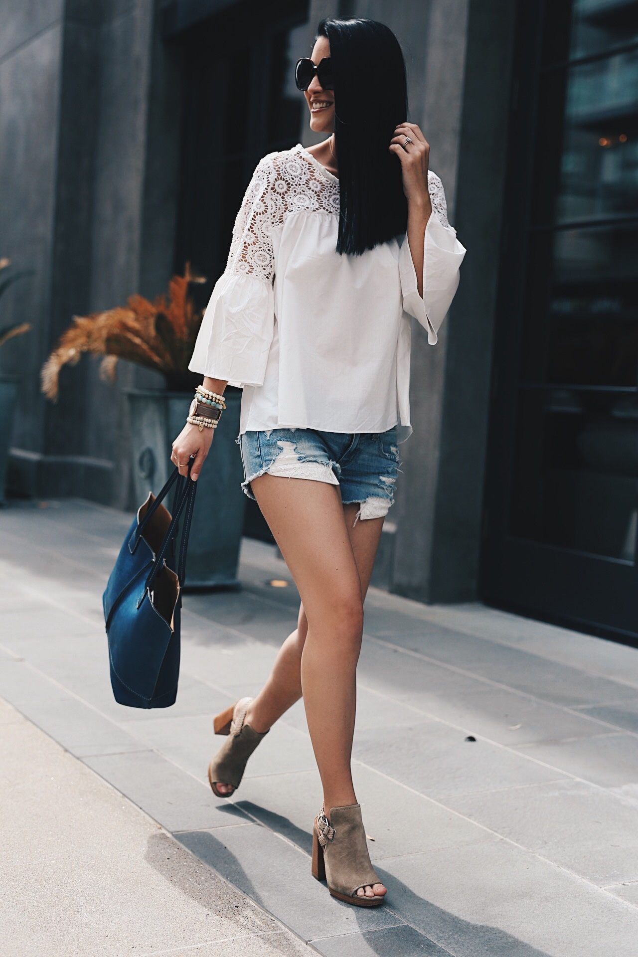 White Crochet Blouse featured by top US fashion blog Dressed to Kill; Image of a woman wearing Chicwish top, American eagle cut off shorts, Frye shoes and tote.