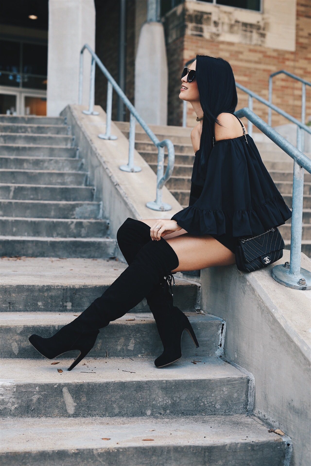 black off-the-shoulder ruffle romper and black OTK boots