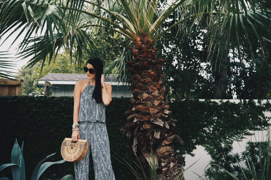 DTKAustin shares details on one of her go-to women's boutiques; Red Dress Boutique along with this beautiful palm print jumpsuit and bamboo bag.
