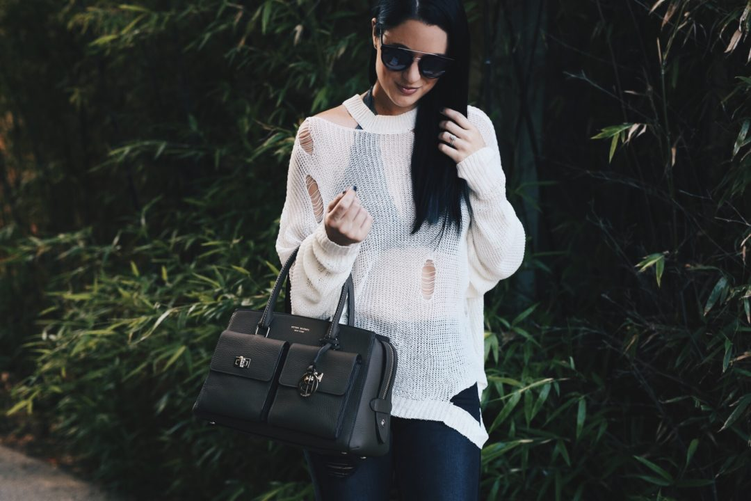 Austin Blogger DTKAustin is sharing how to pull off a sheer distressed sweater with ripped denim and how to still look put together. Handbag from Henri Bendel, sweater from Chicwish and denim from Express. Click for more photos and info.