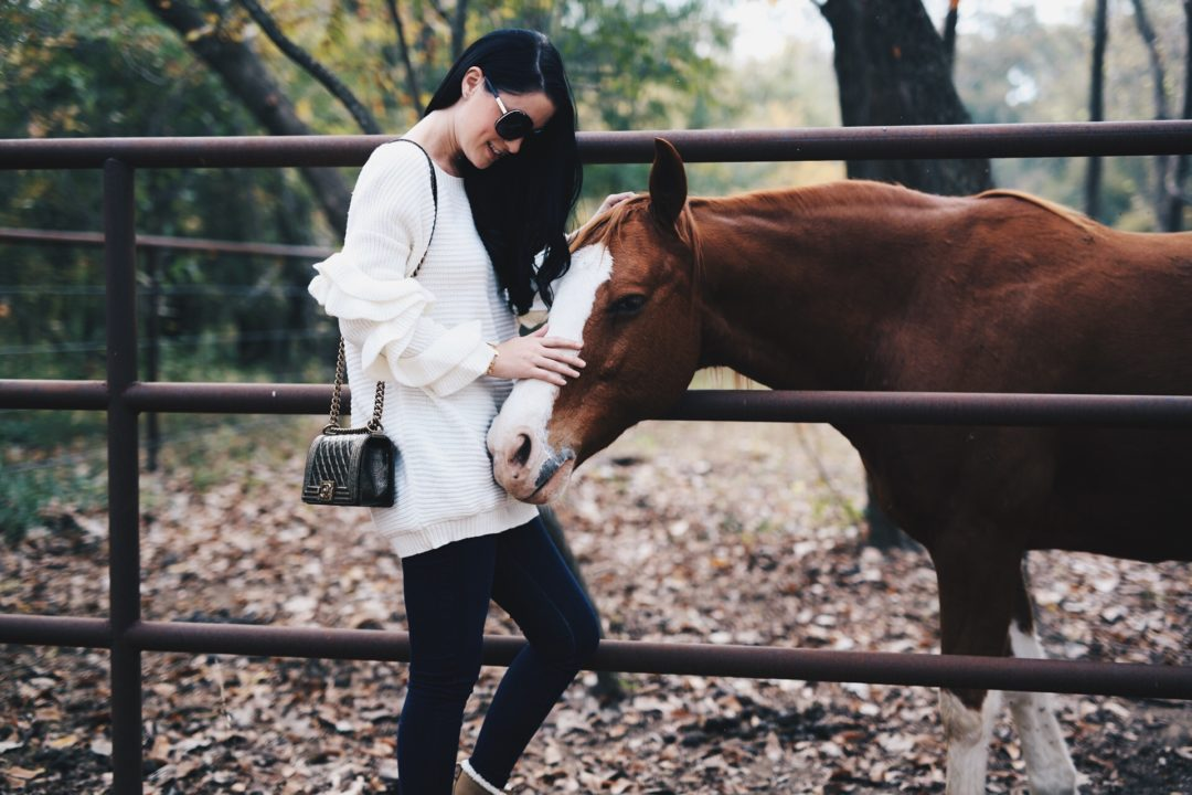 Austin Blogger DTKAustin shares staple ruffle sleeve sweater from Chicwish that is under $100 worn with Sorel snow boots in the Texas country.