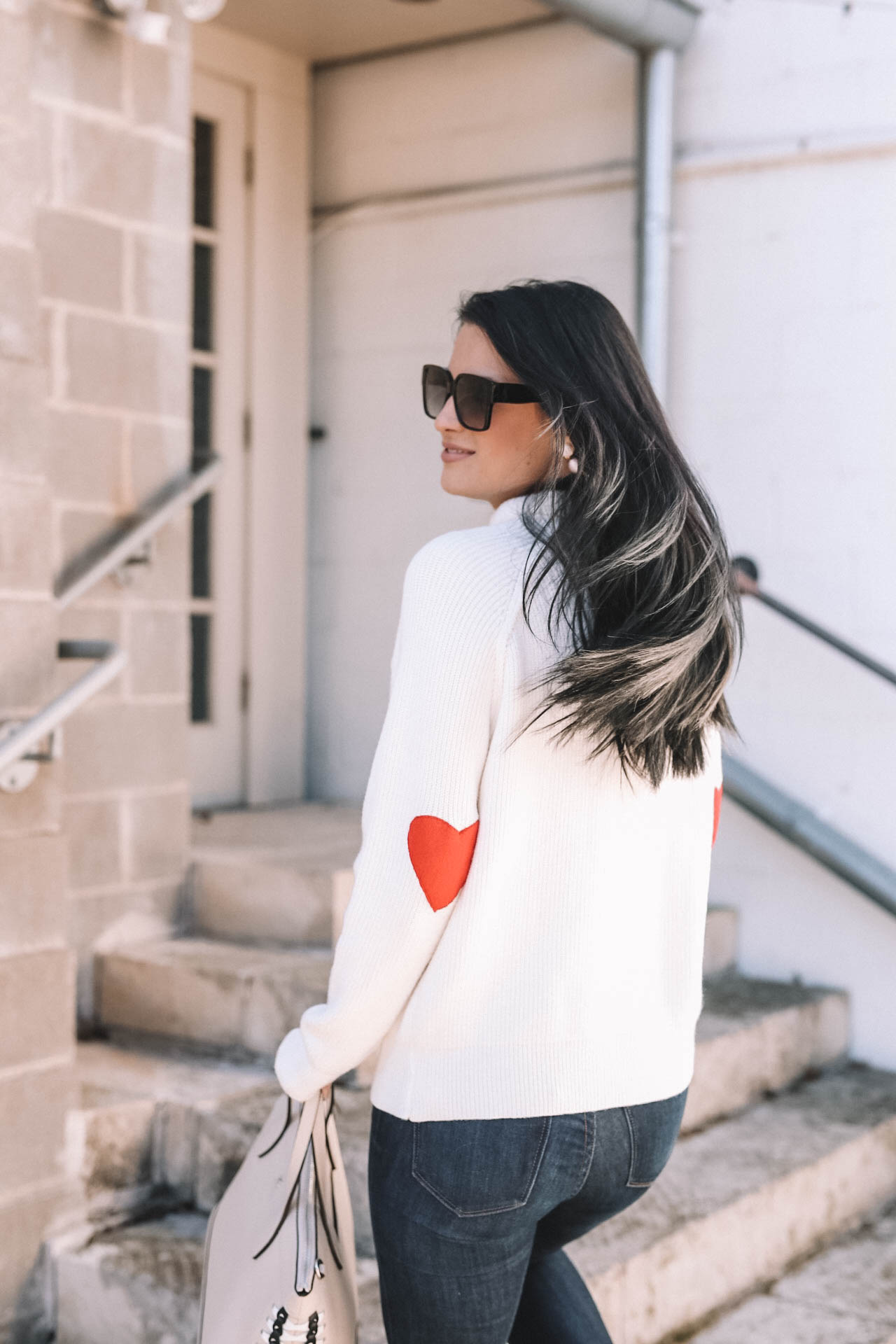 DTKAustin shares why she is dressing casual for Valentine's Day with this heart sleeve Chicwish turtleneck sweater. Valentines Day outfit styled by top US fashion blog, Dressed to Kill: image of a woman wearing a Chicwish heart sweater, Mott & Bow jeans, Steve Madden shoes, Henri Bendel bag, Yves Saint Lauren glasses and Baublebar glasses