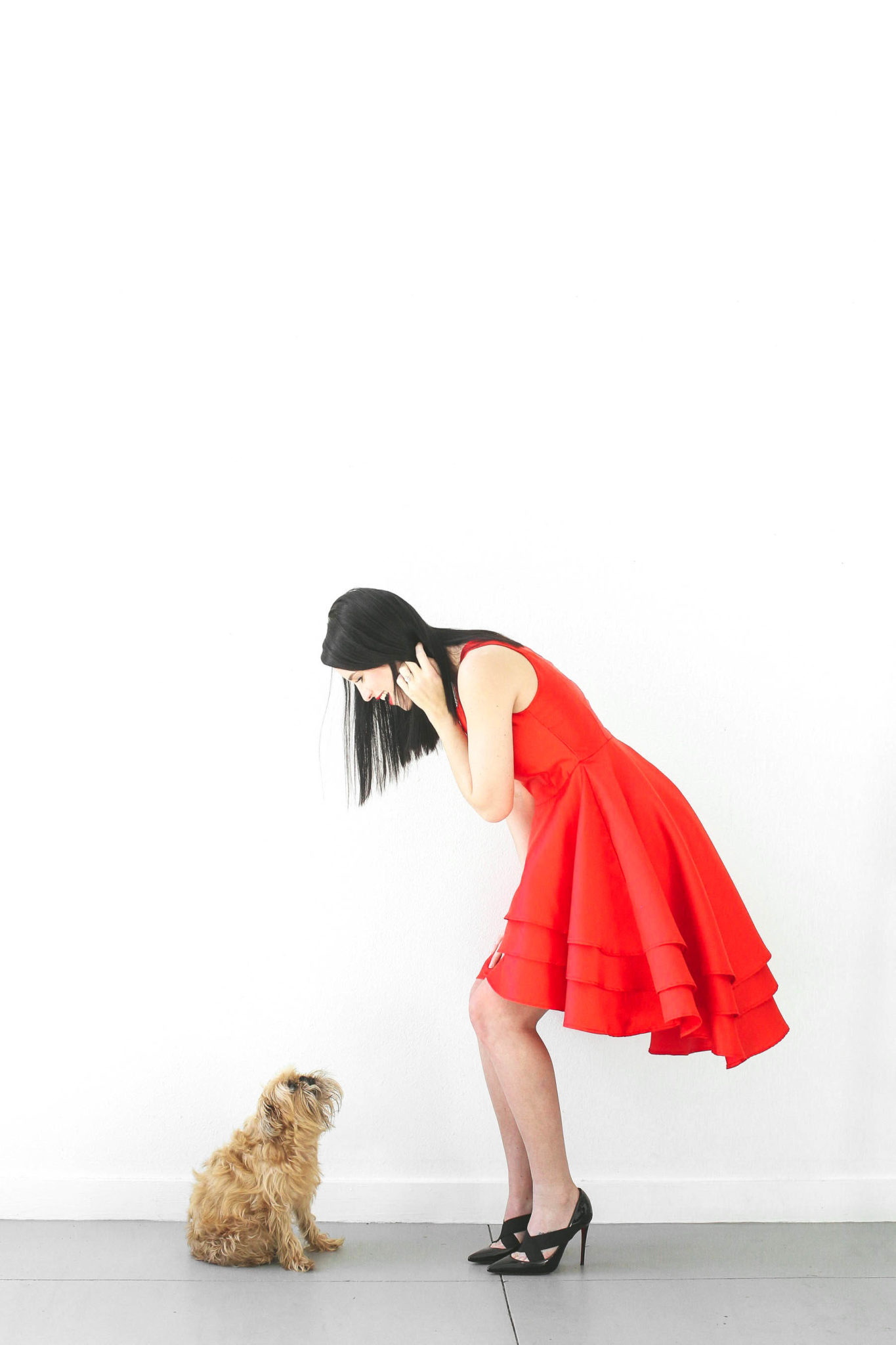 12 Must Have Little Red Dresses for Galentine's Day | classy red dresses | red dress outfit | valentine's day outfit | Valentine's Day dress || Dressed to Kill #reddress #valentinedress #valentineoutfit | Little Red Dresses for Galentine's Day by top US fashion blog, Dressed to Kill: image of a woman looking at a small dog and wearing a Jill Jill Stuart red dress, Kelly Wynne bag and Steve Madden shoes