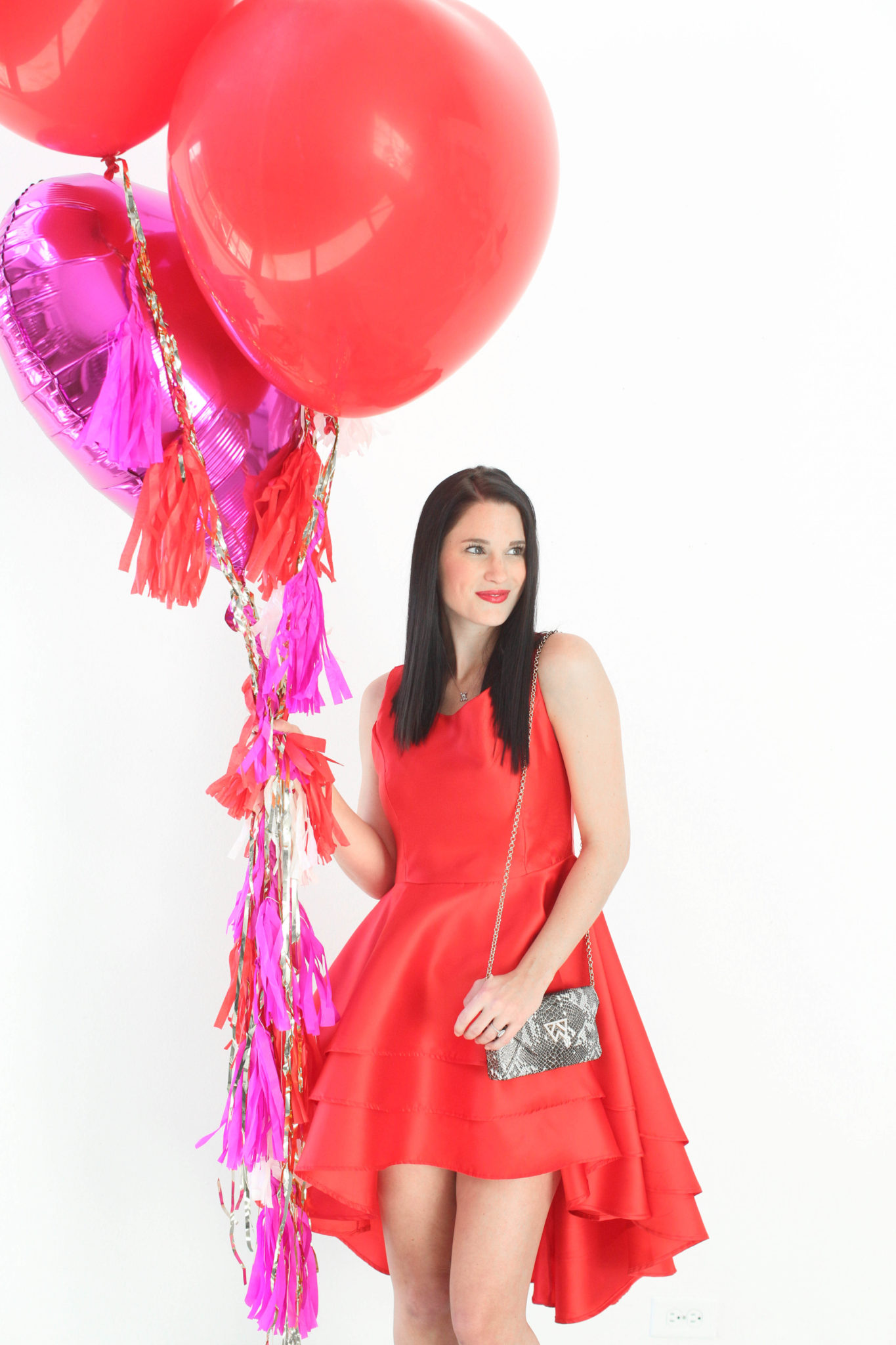 12 Must Have Little Red Dresses for Galentine's Day | classy red dresses | red dress outfit | valentine's day outfit | Valentine's Day dress || Dressed to Kill #reddress #valentinedress #valentineoutfit |Little Red Dresses for Galentine's Day by top US fashion blog, Dressed to Kill: image of a woman holding balloons and wearing a Jill Jill Stuart red dress, Kelly Wynne bag and Steve Madden shoes