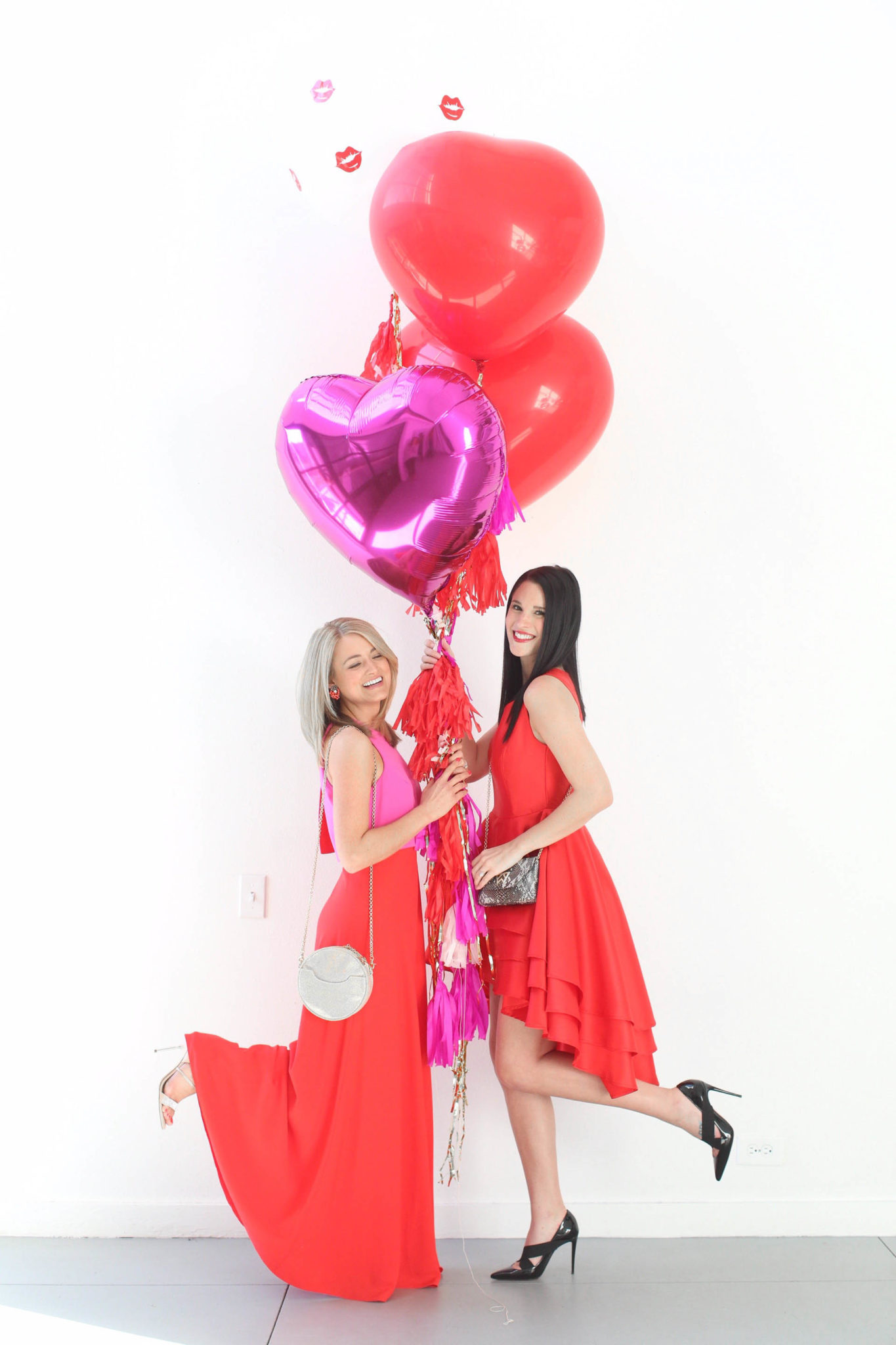 12 Must Have Little Red Dresses for Galentine's Day | classy red dresses | red dress outfit | valentine's day outfit | Valentine's Day dress || Dressed to Kill #reddress #valentinedress #valentineoutfit | Little Red Dresses for Galentine's Day featured by top US fashion blog, Dressed to Kill: image of 2 women holding balloons and wearing a Jill Jill Stuart red dress, Kelly Wynne bag and Steve Madden shoes for the first women and a red Chiwish dress, Christian Louboutin shoes and Kelly Wynne bag on the other woman.