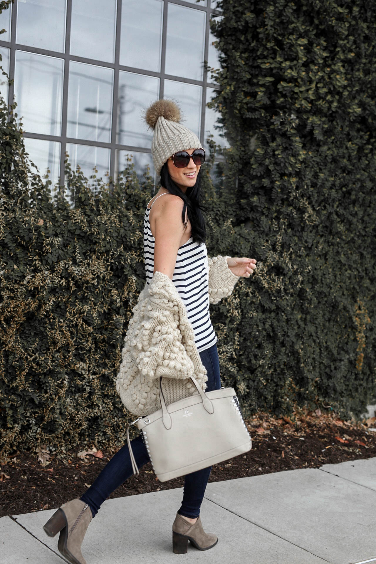 Wardrobe Staples featured by top US fashion blog Dressed to Kill; Image of a woman wearing Chicwish cardigan, CamiNYC cami, Mott & Bow jeans, Lucky booties, Henri Bendel handbag, T&J Designs beanie and Nordstrom sunglasses.