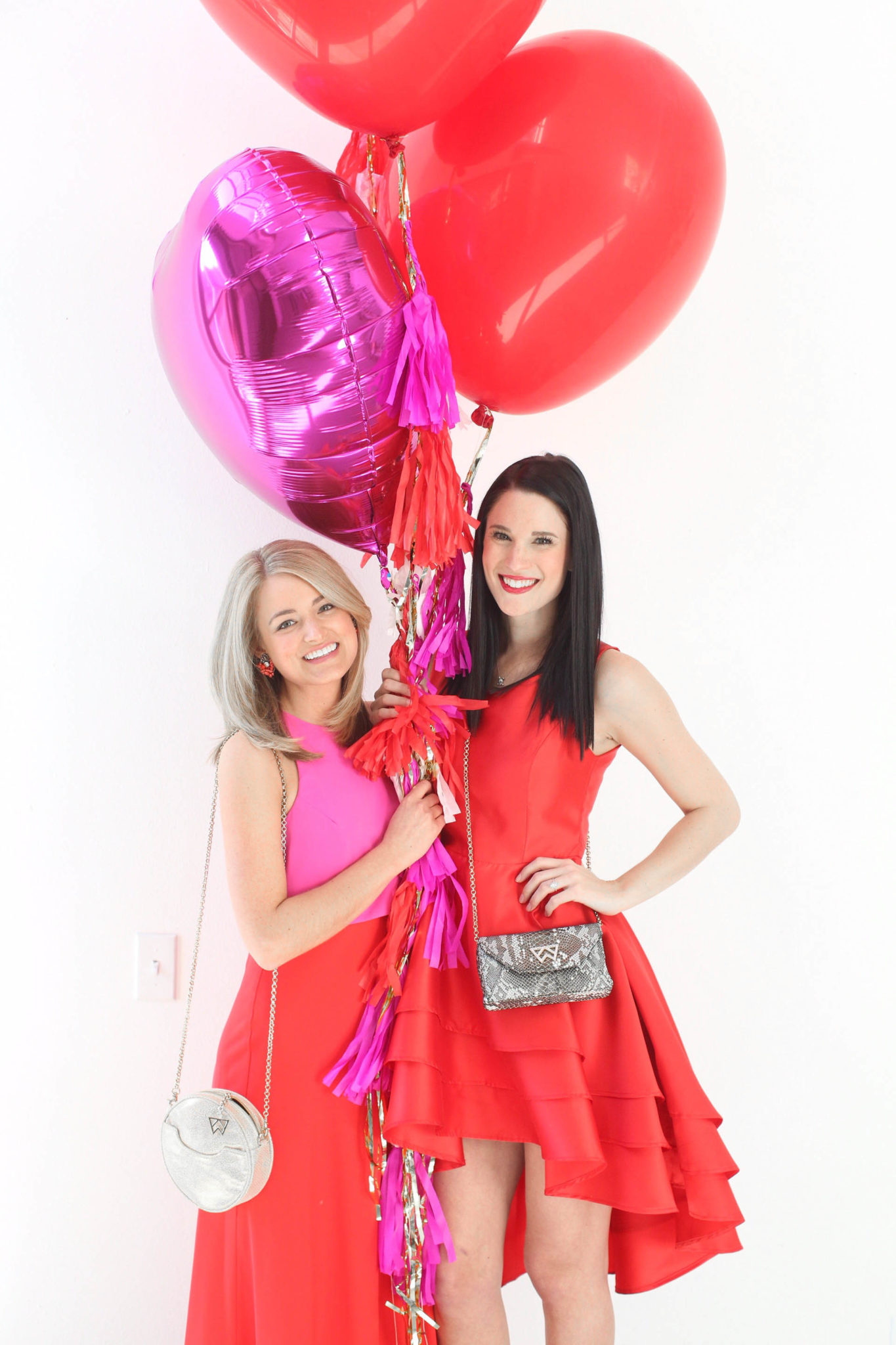 12 Must Have Little Red Dresses for Galentine's Day | classy red dresses | red dress outfit | valentine's day outfit | Valentine's Day dress || Dressed to Kill #reddress #valentinedress #valentineoutfit | Little Red Dresses for Galentine's Day by popular US fashion blog, Dressed to Kill: image of 2 women holding balloons and wearing a Jill Jill Stuart red dress, Kelly Wynne bag and Steve Madden shoes for the first women and a red Chiwish dress, Christian Louboutin shoes and Kelly Wynne bag on the other woman.