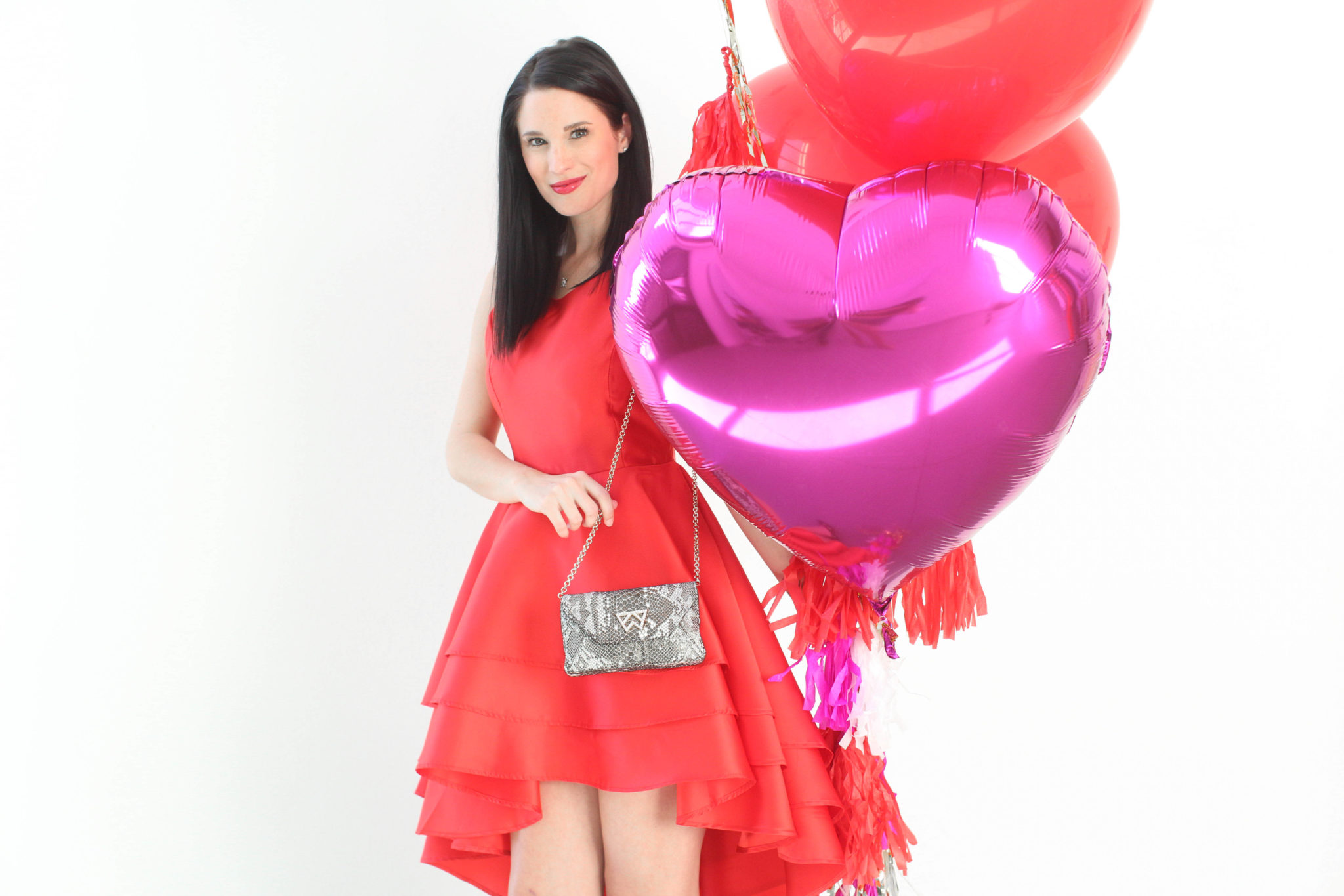 DTKAustin is sharing 12 little red dresses for Valentine's and Galentine's Day. | Little Red Dresses for Galentine's Day by top US fashion blog, Dressed to Kill: image of a woman holding balloons and wearing a Jill Jill Stuart red dress, Kelly Wynne bag and Steve Madden shoes