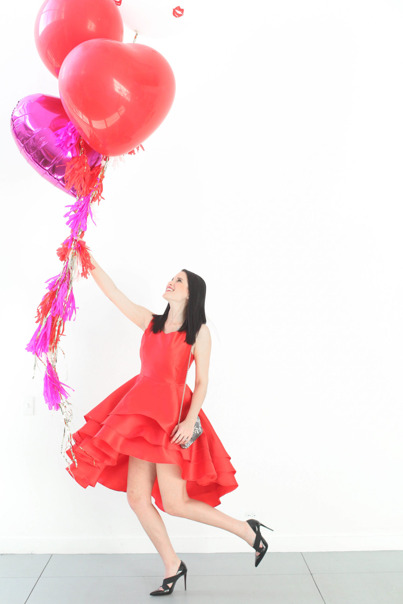 12 Must Have Little Red Dresses for Galentine's Day | classy red dresses | red dress outfit | valentine's day outfit | Valentine's Day dress || Dressed to Kill #reddress #valentinedress #valentineoutfit | Little Red Dresses for Galentine's Day by top US fashion blog, Dressed to Kill: image of a woman holding balloons and wearing a Jill Jill Stuart red dress, Kelly Wynne bag and Steve Madden shoes.