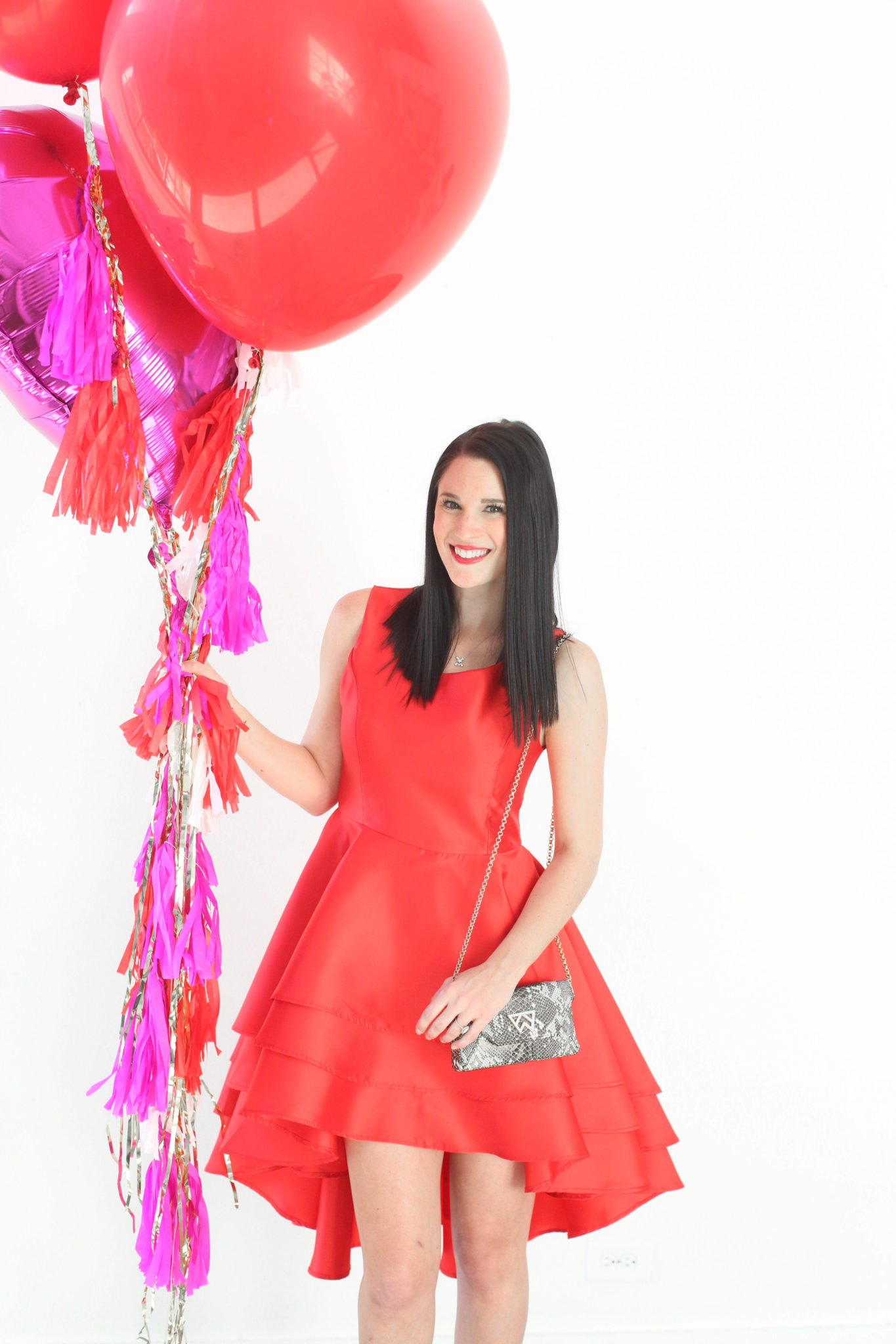12 Must Have Little Red Dresses for Galentine's Day | classy red dresses | red dress outfit | valentine's day outfit | Valentine's Day dress || Dressed to Kill #reddress #valentinedress #valentineoutfit | Little Red Dresses for Galentine's Day by top US fashion blog, Dressed to Kill: image of a woman holding balloons and wearing a Jill Jill Stuart red dress, Kelly Wynne bag and Steve Madden shoes