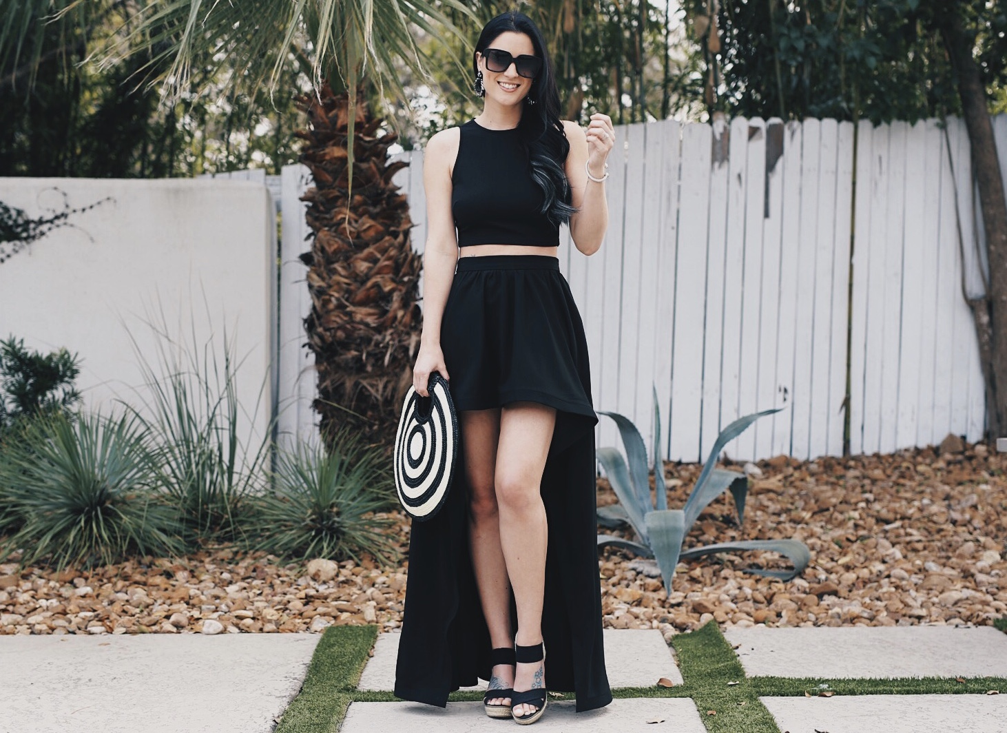 DTKAustin shares one of her most dramatic summer looks; a back two piece, high low skirt set from Akira with a straw round bag from Anthropologie.