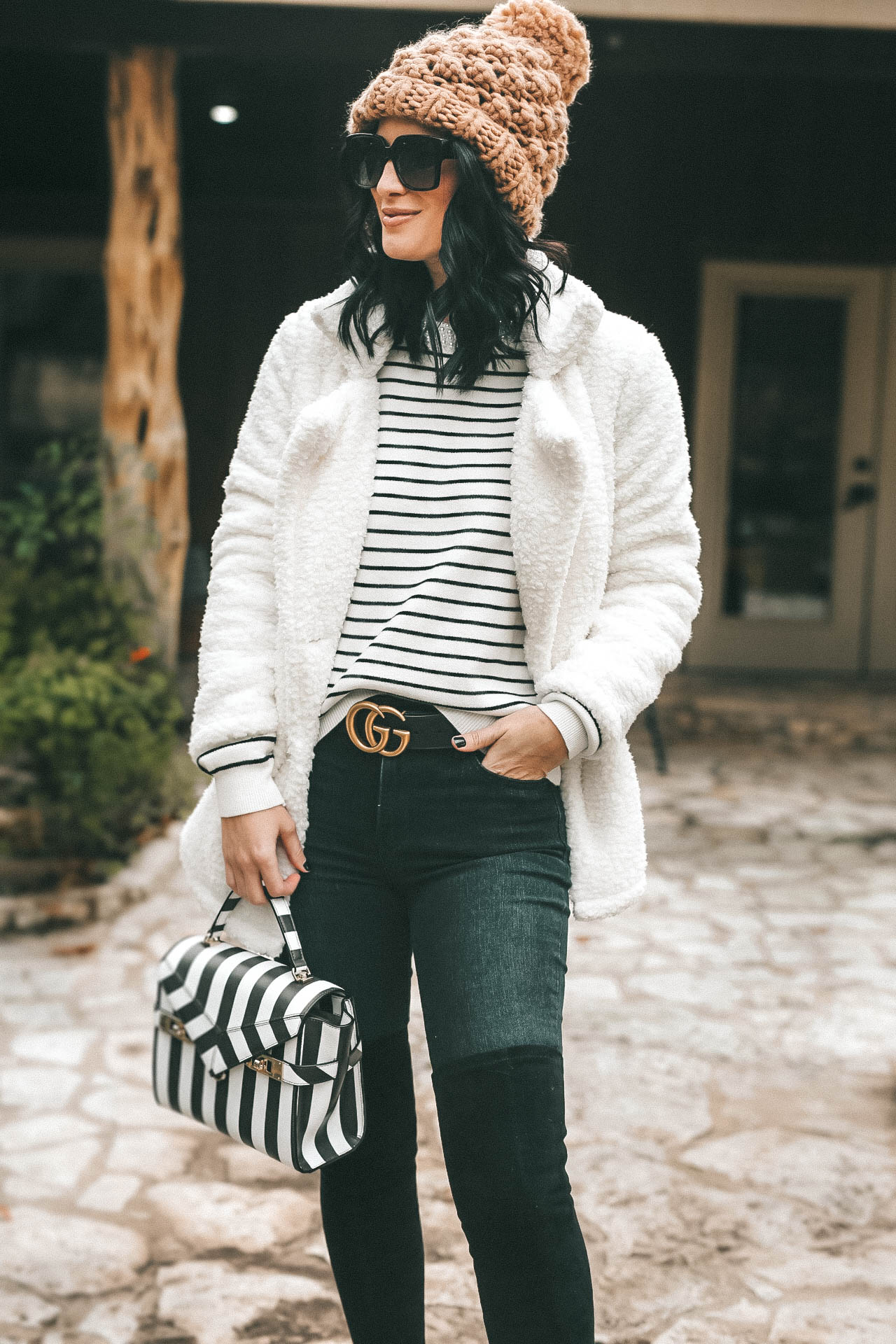 DTKAustin is sharing the most affordable beaded striped sweater from Chicwish. It is hand beaded with faux pearls and on sale for $45. Handbag is Henri Bendel, Over the Knee Boots Goodnight Macaroon, Teddy Bear coat is Goodnight Macaroon, Knit beanie is Abercrombie. | Knit sweater for winter | how to style a striped sweater | How to style stripes || #fashion #style #womensoutfit #womensfashion #stripedsweater #knit #knitsweater #winterstyle #streetstyle #winterfashion #dtkaustin | How to style a striped sweater featured by top Austin fashion blog, Dressed to Kill: image of a woman wearing a Goodnight Macaroon teddy bear coat, a Chicwish striped sweater, Levi's skinny jeans, Goodnight Macaroon over the knee boots, Henri Bendel satchel, Gucci leather belt, Nordstrom Pompom beanie