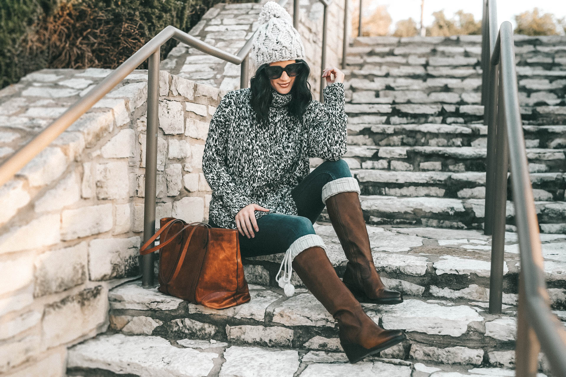 DTKAustin is sharing the best investment boots for Fall and Winter with Frye and Zappos. Ashley is wearing Knee high pom pom socks from UGG, skinny jeans from Levis, a chunky knit beanie from Sole Society, Melissa Frye Tote and a knit sweater from Nordstrom. || Dressed to Kill #winterboots #womensboots #fryeboots #dtkaustin