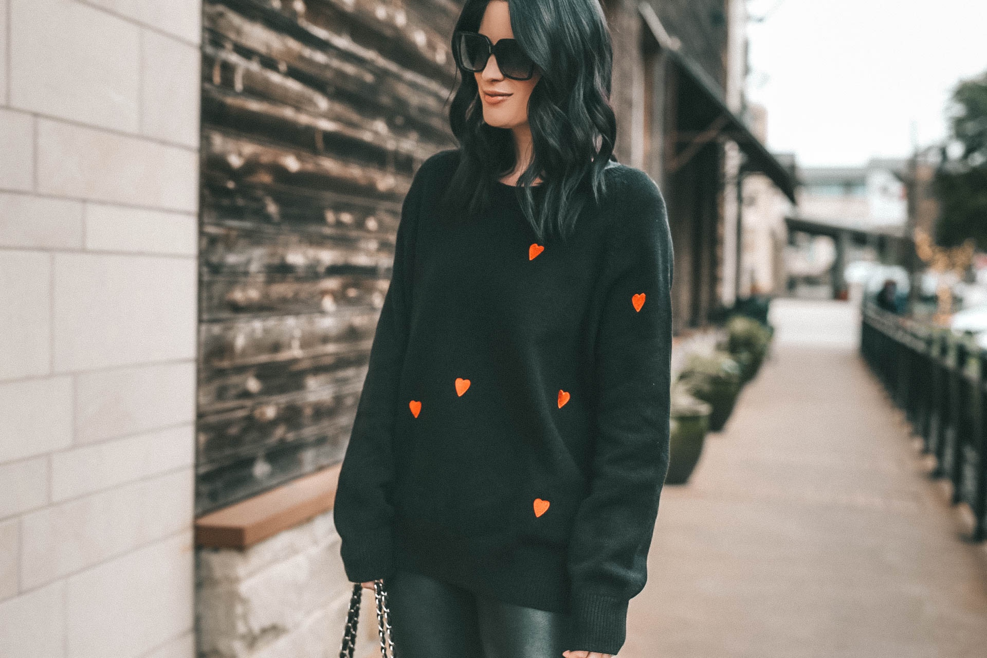 Cute Heart Sweaters featured by top US fashion blog Dressed to Kill; Image of a woman wearing Chicwish sweater, Nordstrom leggings, Goodnight Macaroon boots, YSL sunglasses and Chanel bag.