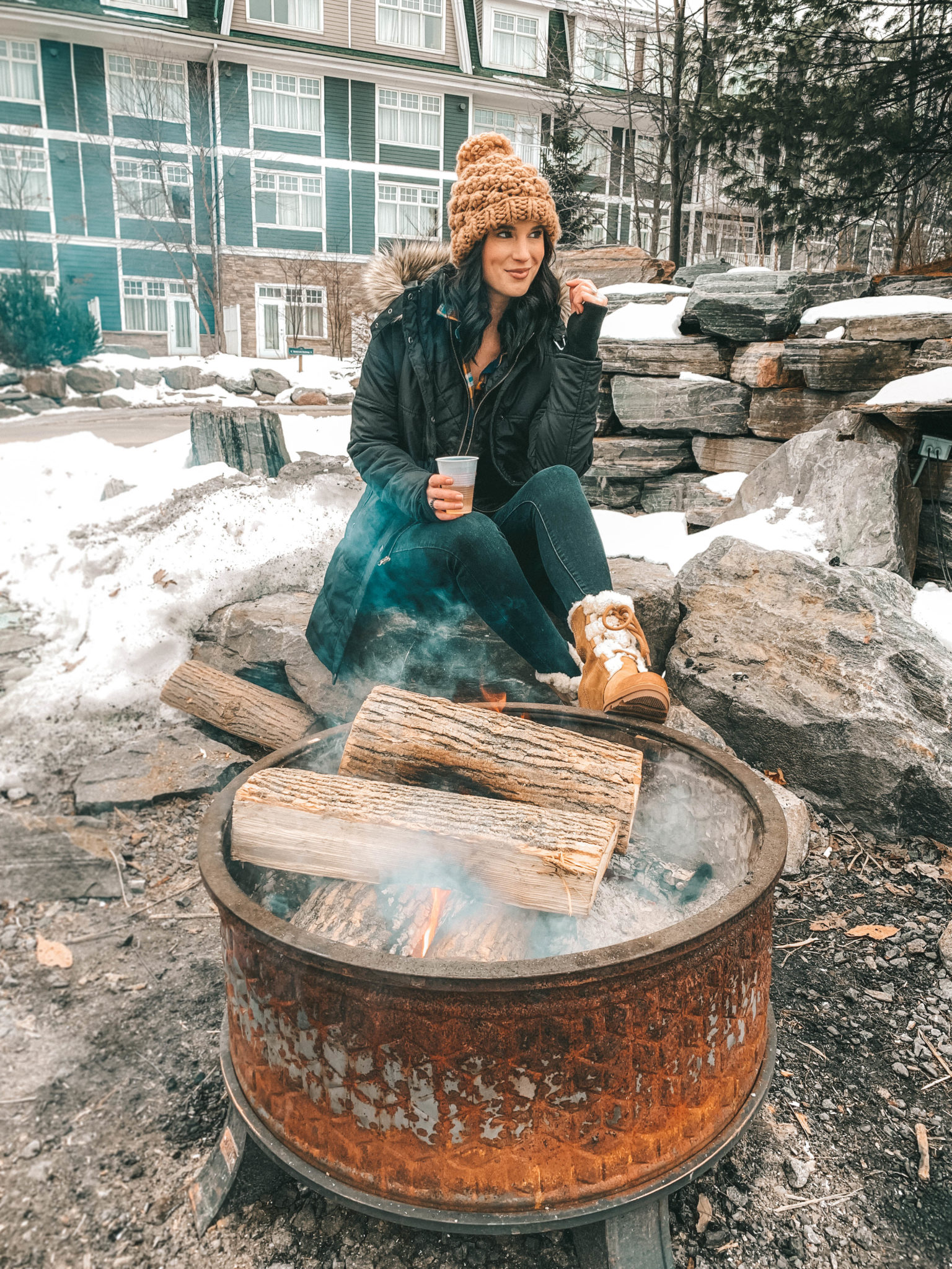 The Rosseau Muskoka featured by top US travel blog Dressed to Kill; Girl wearing a brown beanie sitting by a campfire.