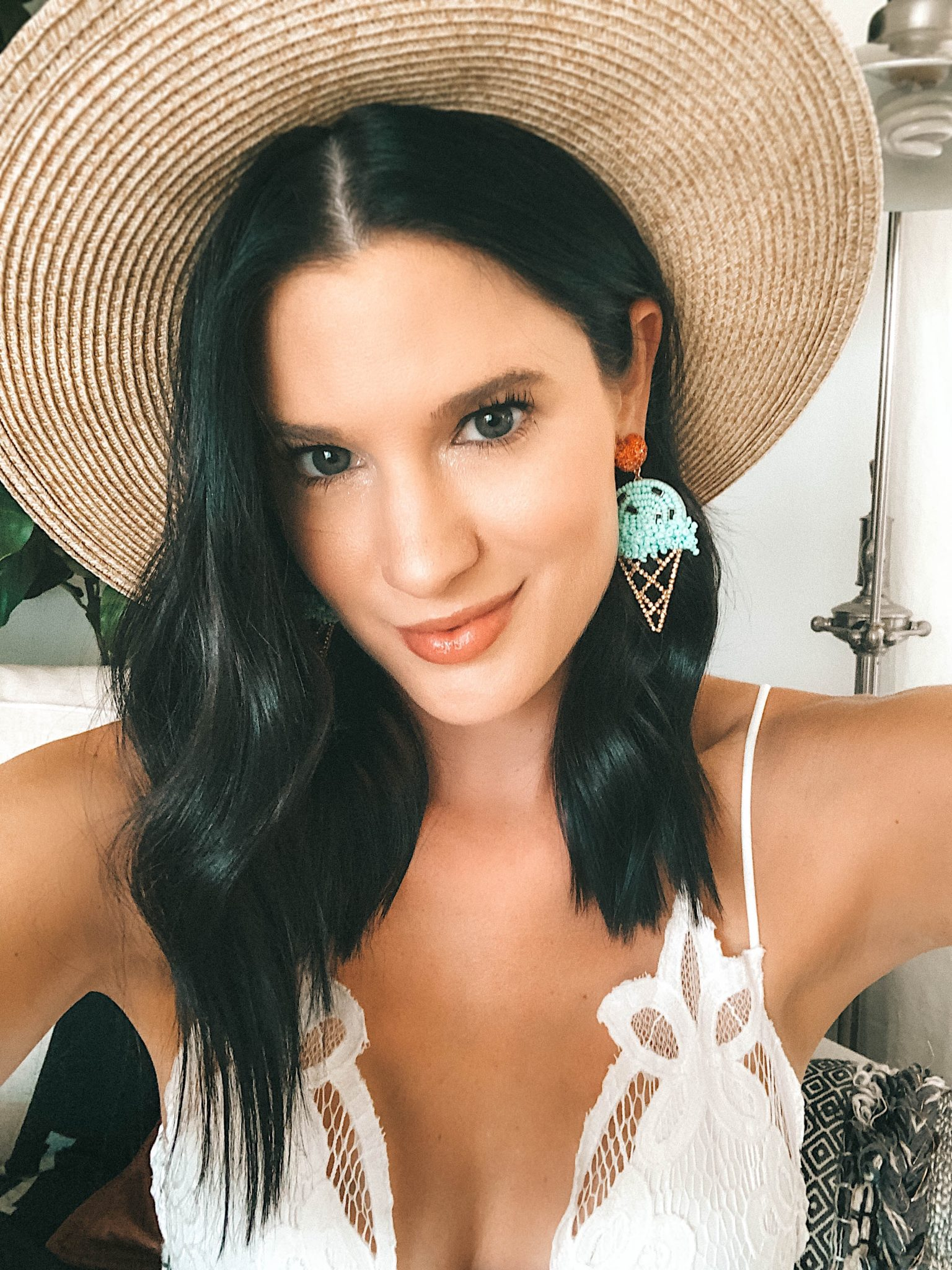 16 Affordable Statement Earrings for Summer by popular Austin fashion blog, Dressed to Kill: close up image of a women in a straw sunhat, white lace top with plunging neck and Baublebar ice cream statement earrings.