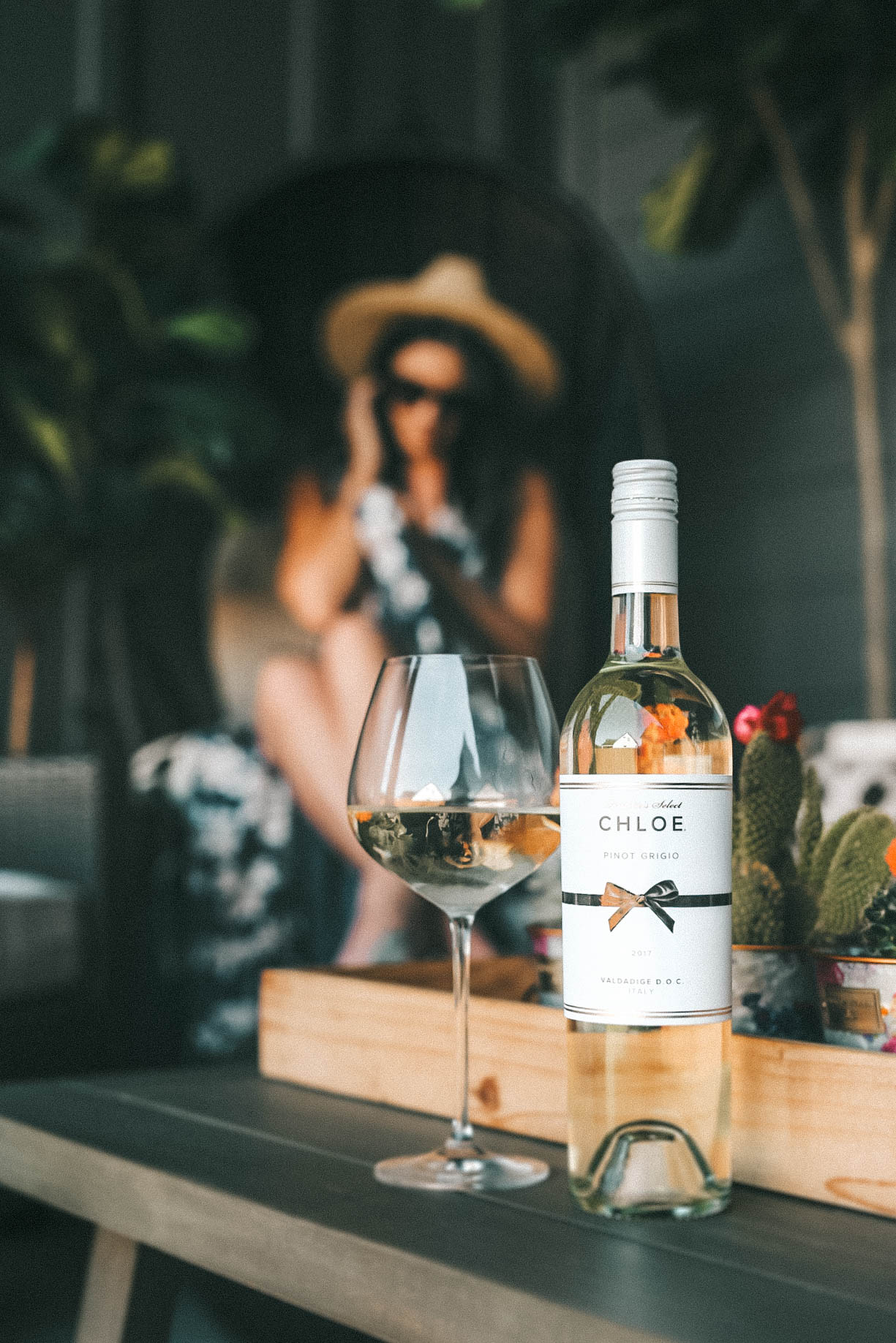 Celebrating Women in Film with Chloe Wine Collection by popular Austin life and style blog, Dressed to Kill: image of a woman sitting behind a bottle of Chloe pinot grigio wine and an empty wine glass that are resting on a wooden coffee table.