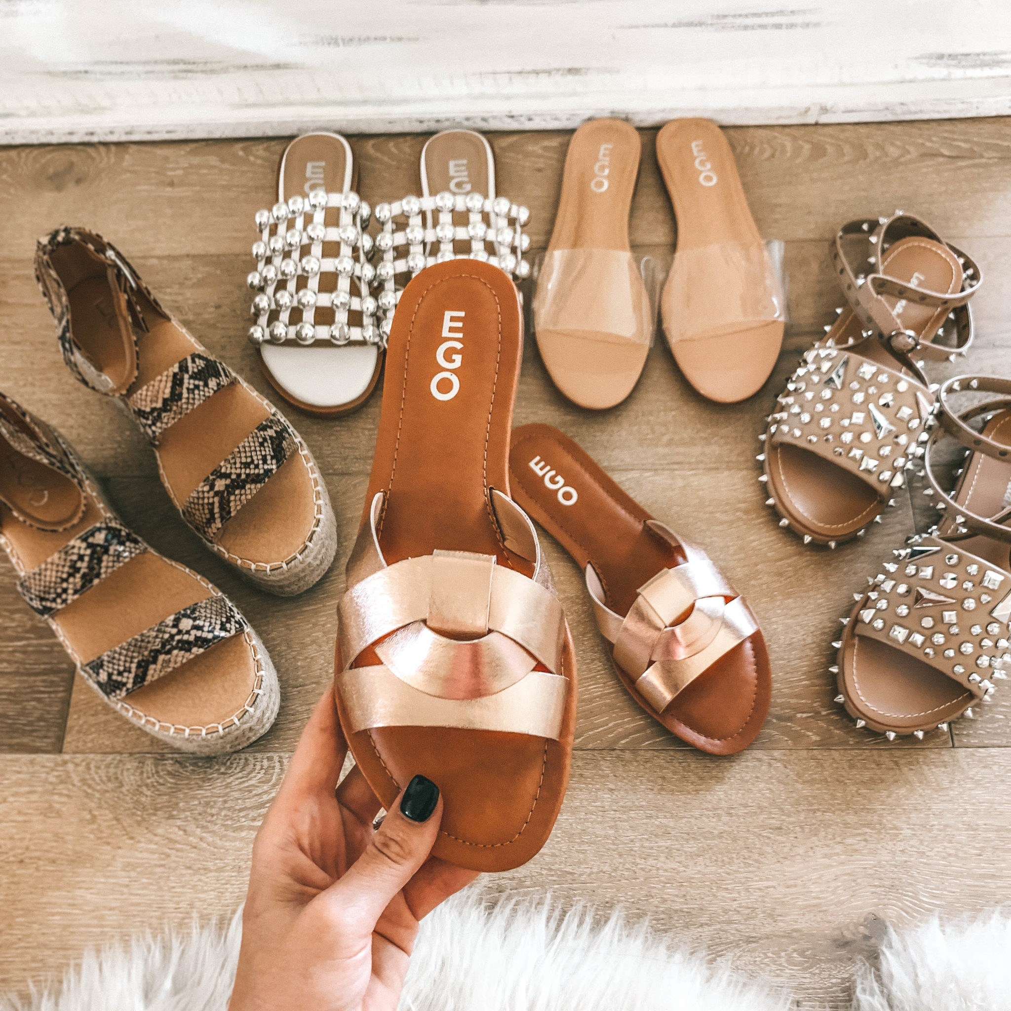 5 Must Have Affordable EGO Sandals for Summer by popular Austin fashion blog, Dressed to Kill: image of woman holding EGO sandals Billie Flat Sandal In Rose Gold Faux Leather.
