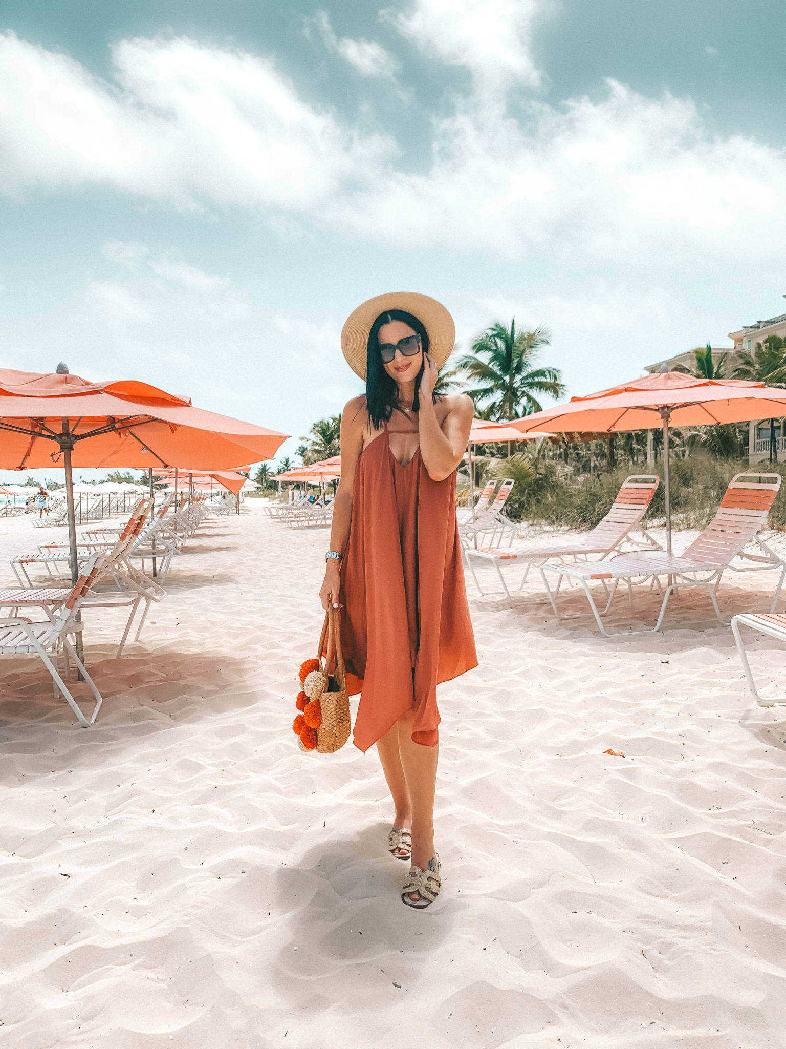 Amaryllis Apparel Abroad Turks & Caicos Summer Try-On by popular Austin fashion blog, Dressed to Kill: image of a woman standing outside on a beach in Turks and Caicos and wearing an Amaryllis Apparel rust colored Breezy Day Dress.