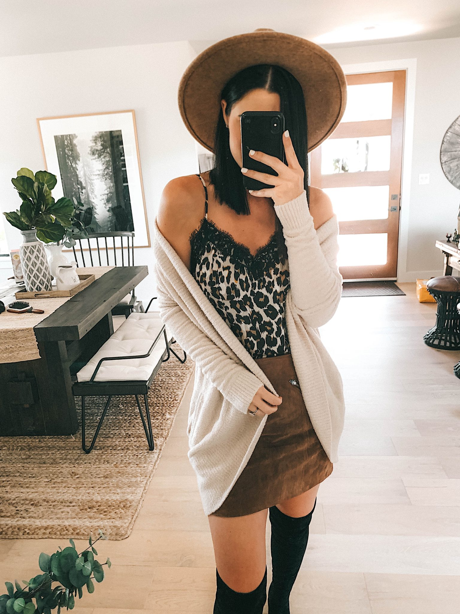 Create a Capsule Wardrobe with Nordstrom Anniversary Sale Pieces by popular Austin fashion blog, Dressed to Kill: image of a woman standing in her house and wearing a Nordstrom BlankNYC Suede Mini Skirt, Barefoot Dreams Cardigan, Steve Madden Over the Knee Boots and BP Lace Cami.