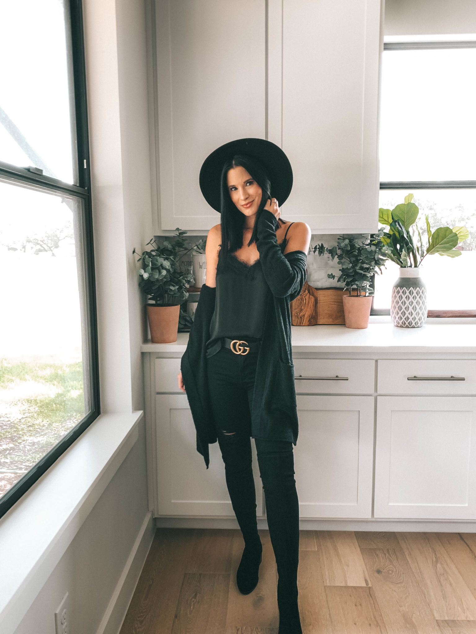 How to Style an All Black Outfit 3 Different Ways by popular Austin blog, Dressed to Kill: image of woman standing in her kitchen and wearing a black Articles of Society Sarah Skinny Ankle Jeans, black Lace Trim Satin Camisole Top, and black Barefoot Dreams CozyChic Lite® Circle Cardigan.