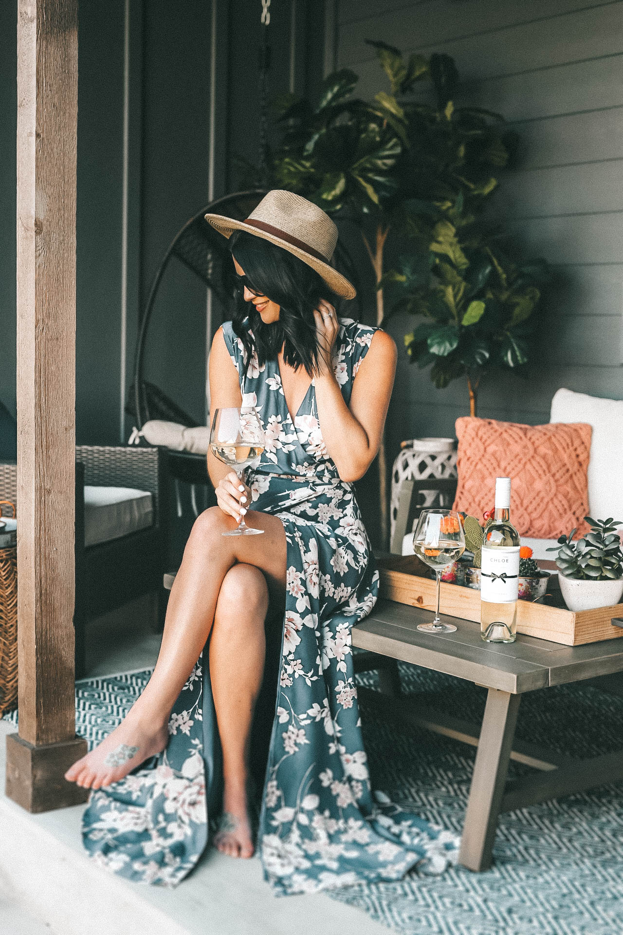 Celebrating Women in Film with Chloe Wine Collection by popular Austin life and style blog, Dressed to Kill: image of a woman sitting on an outdoor coffee table and holding a wine glass with Chloe pinot grigio wine in it with the Chloe wine bottle and another wine glass resting next to her.