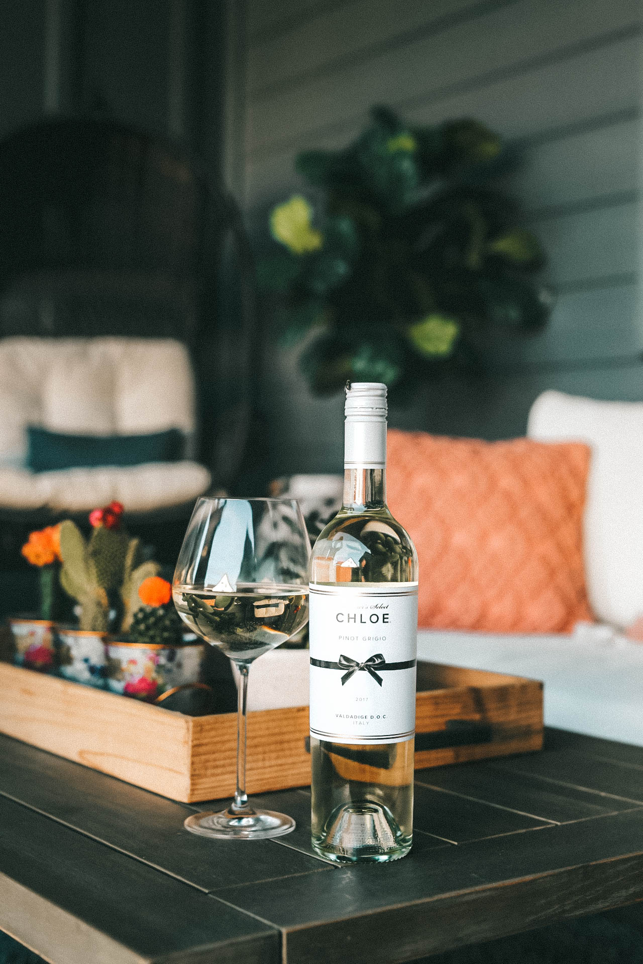 Celebrating Women in Film with Chloe Wine Collection by popular Austin life and style blog, Dressed to Kill: image of a bottle of Chloe pinot grigio wine on a wooden coffee table with a wine glass resting next to it.