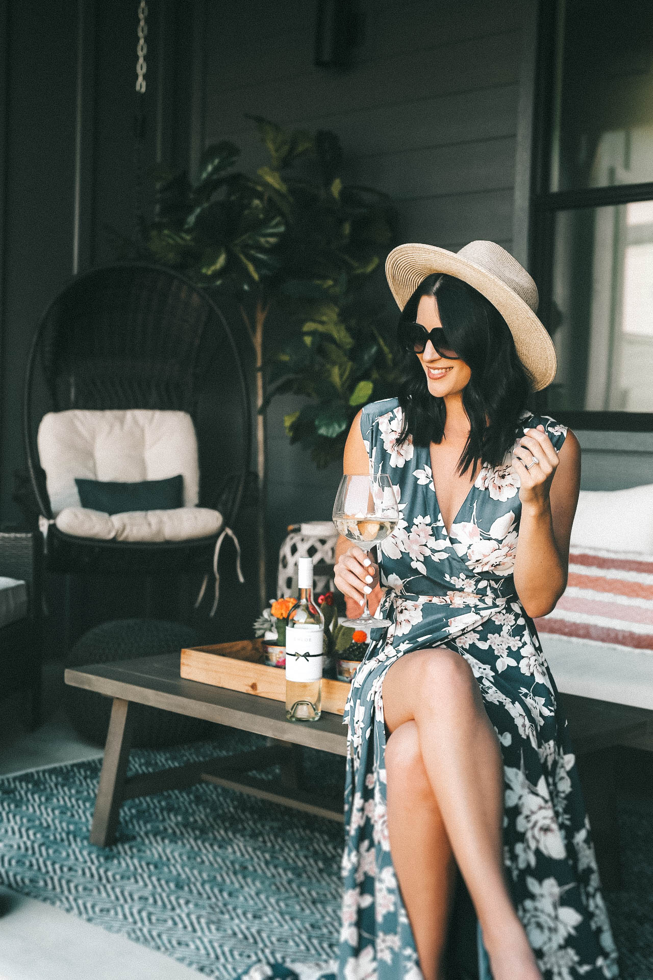 Celebrating Women in Film with Chloe Wine Collection by popular Austin life and style blog, Dressed to Kill: image of a woman sitting on an outdoor coffee table and holding a wine glass with Chloe pinot grigio wine in it with the Chloe wine bottle resting next to her.