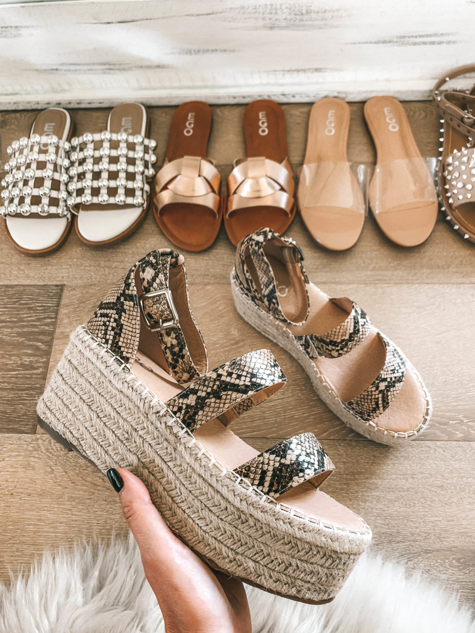 5 Must Have Affordable EGO Sandals for Summer by popular Austin fashion blog, Dressed to Kill: image of woman holding EGO sandals Hazy Espadrille Flatform In Nude Snake Print Faux Leather.