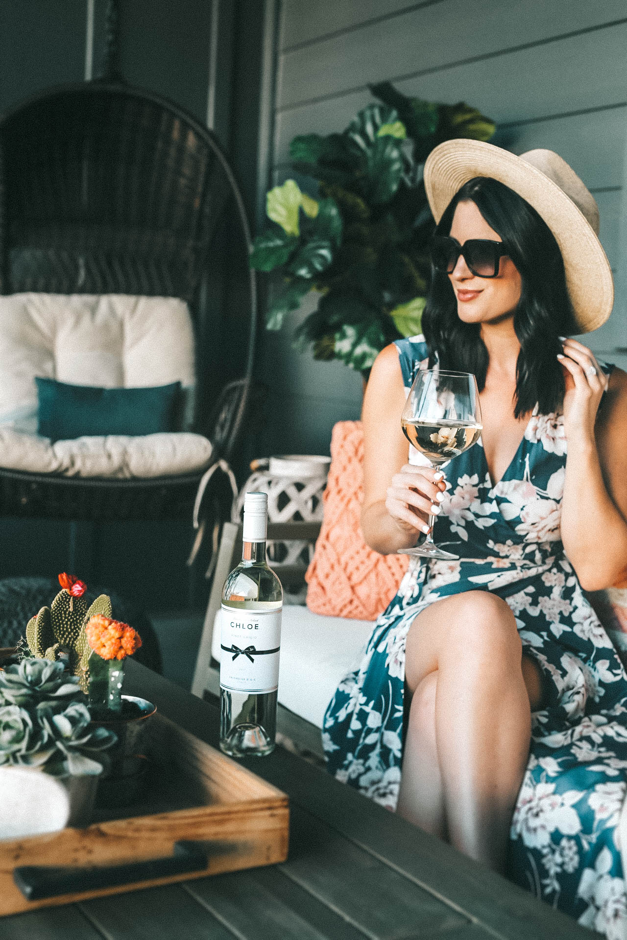 Celebrating Women in Film with Chloe Wine Collection by popular Austin life and style blog, Dressed to Kill: image of a woman sitting outside on her patio next to a bottle of Chloe pinot grigio wine and holding a wine glass in her hand that's half full with the same wine.