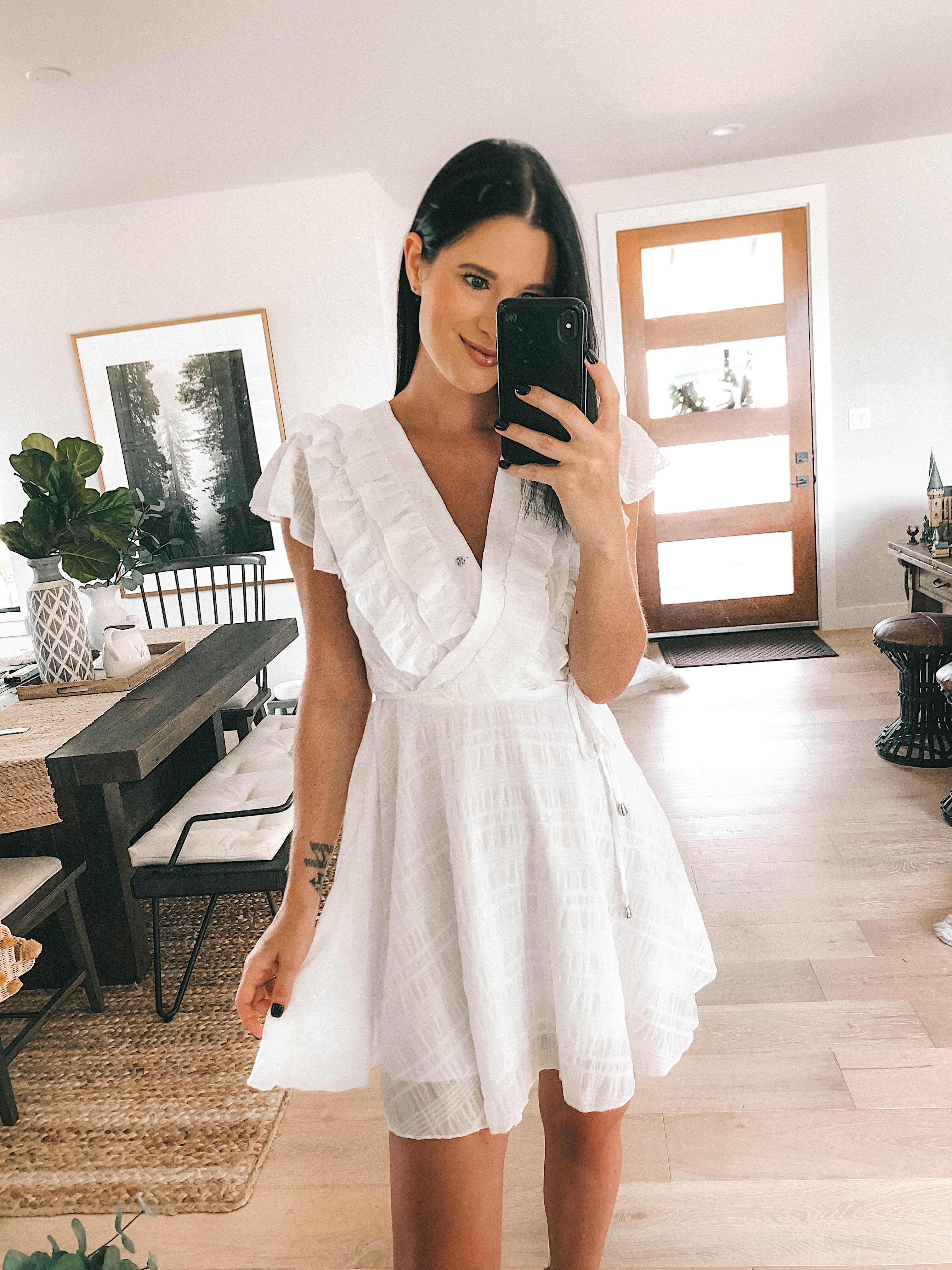 Goodnight Macaroon Summer Dresses Try-On by popular Austin fashion blog, Dressed to Kill: image of a woman standing in her house and wearing a Goodnight Macaroon 'DOBIE' White Ruffle Tie Waist Mini Dress.