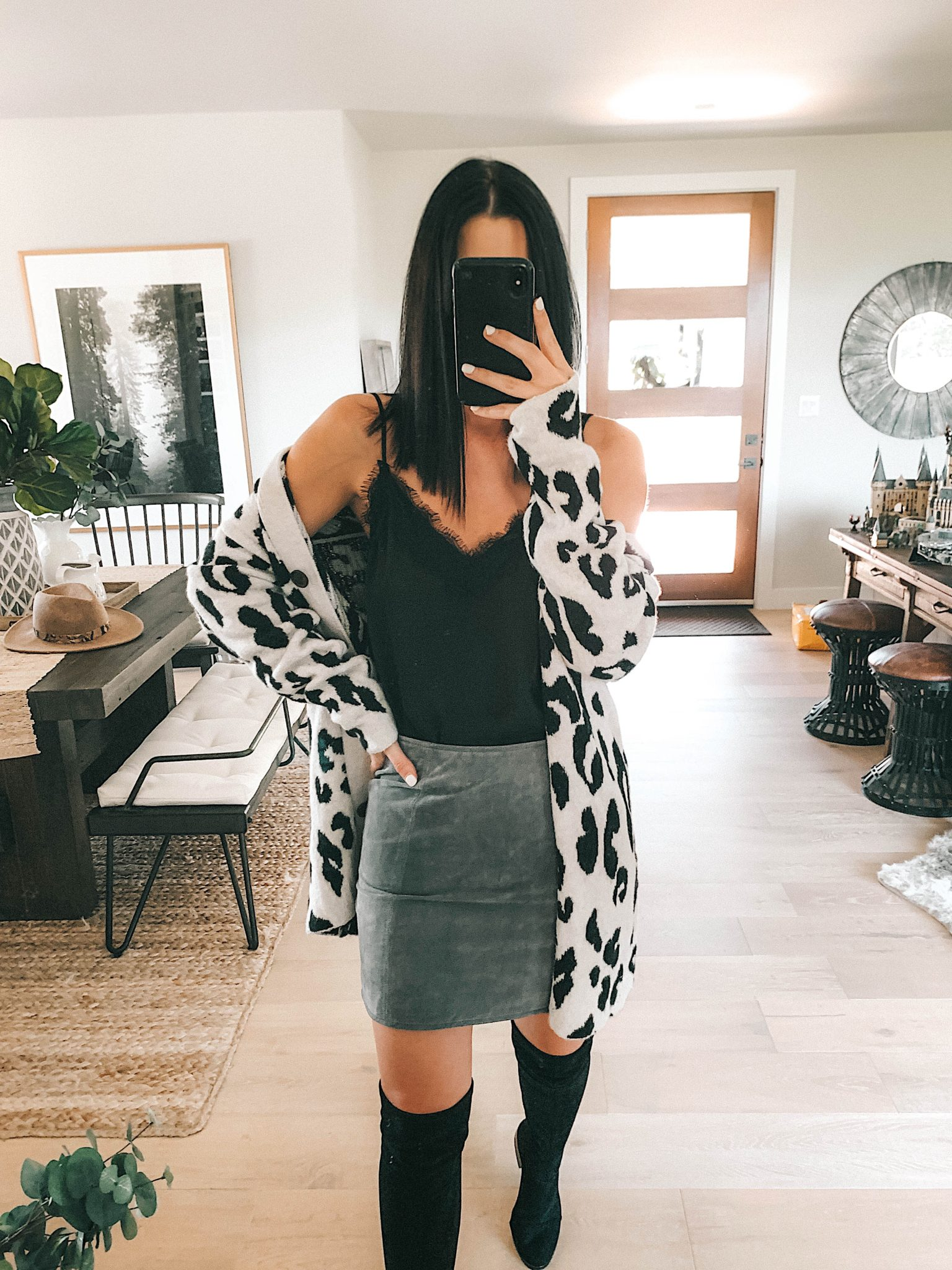 Create a Capsule Wardrobe with Nordstrom Anniversary Sale Pieces by popular Austin fashion blog, Dressed to Kill: image of a woman standing in her house and wearing a Nordstrom BlankNYC Suede Mini Skirt, Steve Madden Over the Knee Boots, leopard print cardigan and BP Lace Cami
