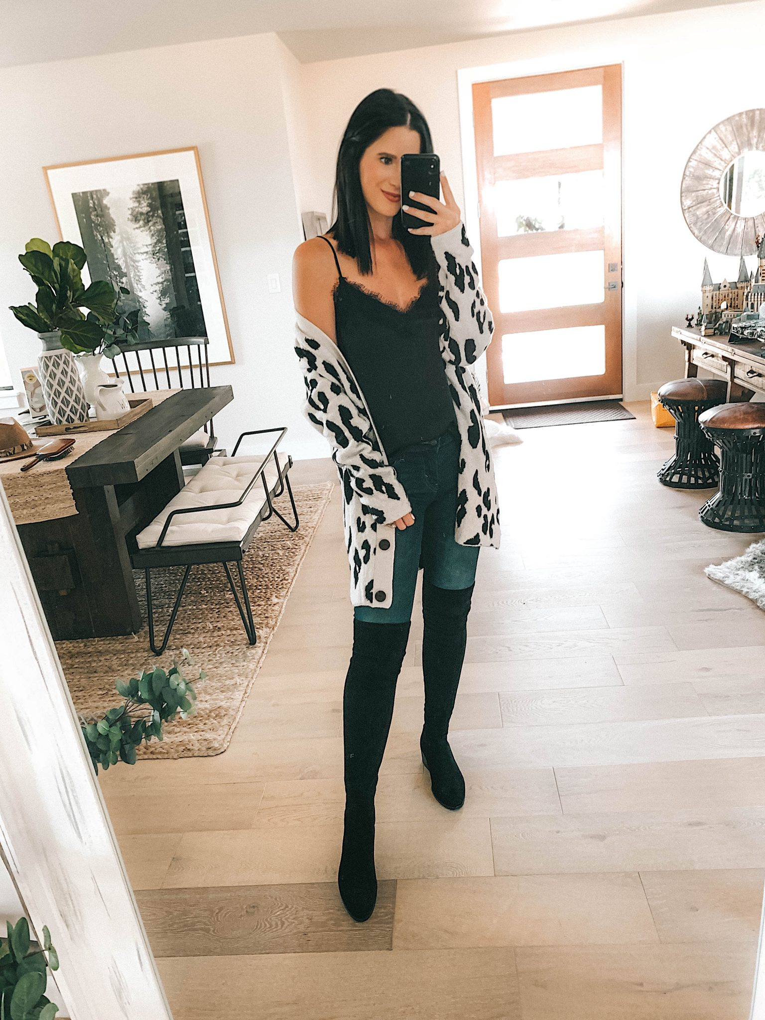 Create a Capsule Wardrobe with Nordstrom Anniversary Sale Pieces by popular Austin fashion blog, Dressed to Kill: image of a woman standing in her house and wearing a Nordstrom leopard print cardigan, BP. lace cami, and Steve Madden over the knee boots.
