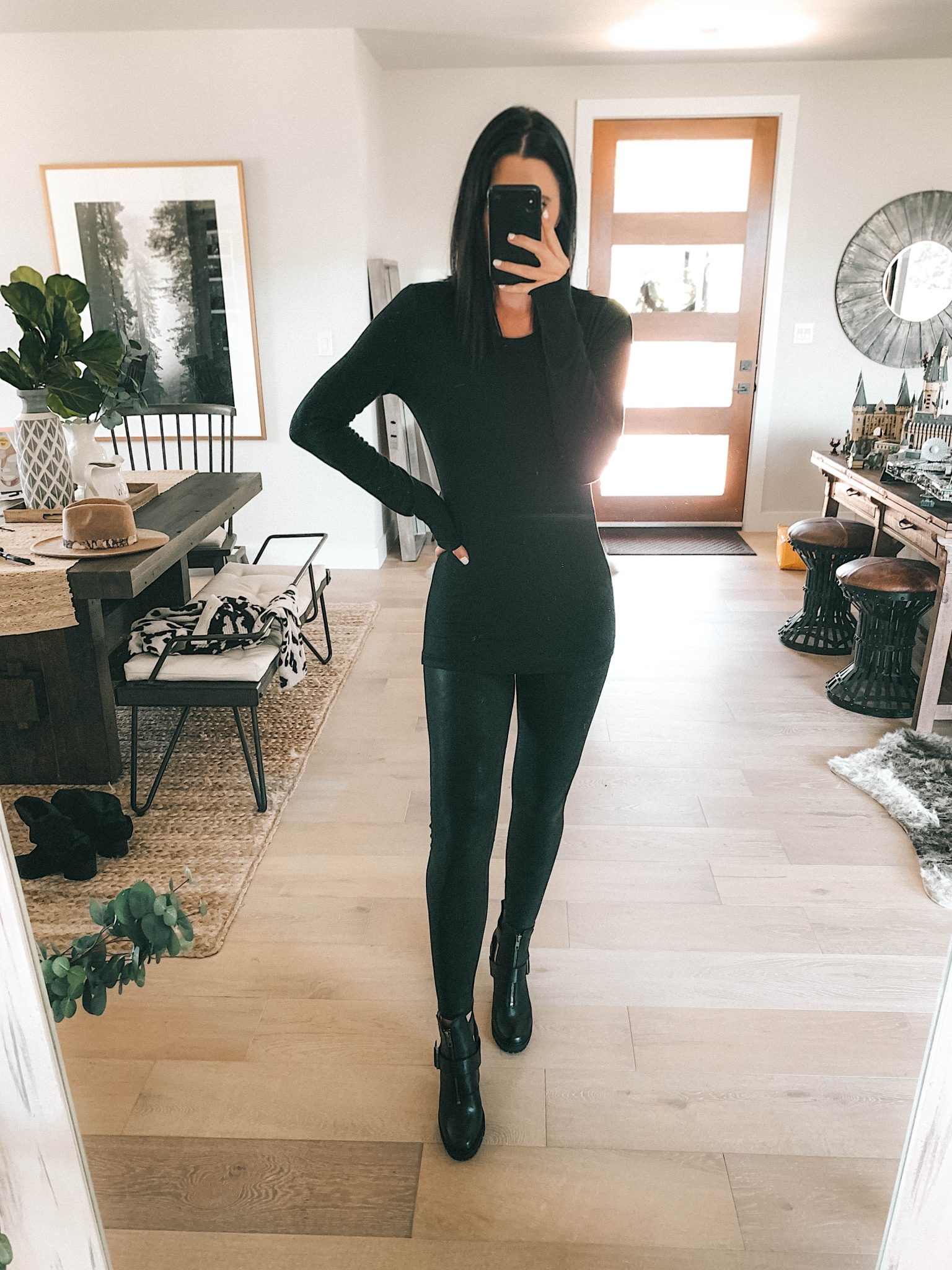 Create a Capsule Wardrobe with Nordstrom Anniversary Sale Pieces by popular Austin fashion blog, Dressed to Kill: image of a woman standing in her house and wearing Steve Madden Black Booties, Spanx Faux Leather Leggings and Nordstrom Signature Cashmere Sweater.