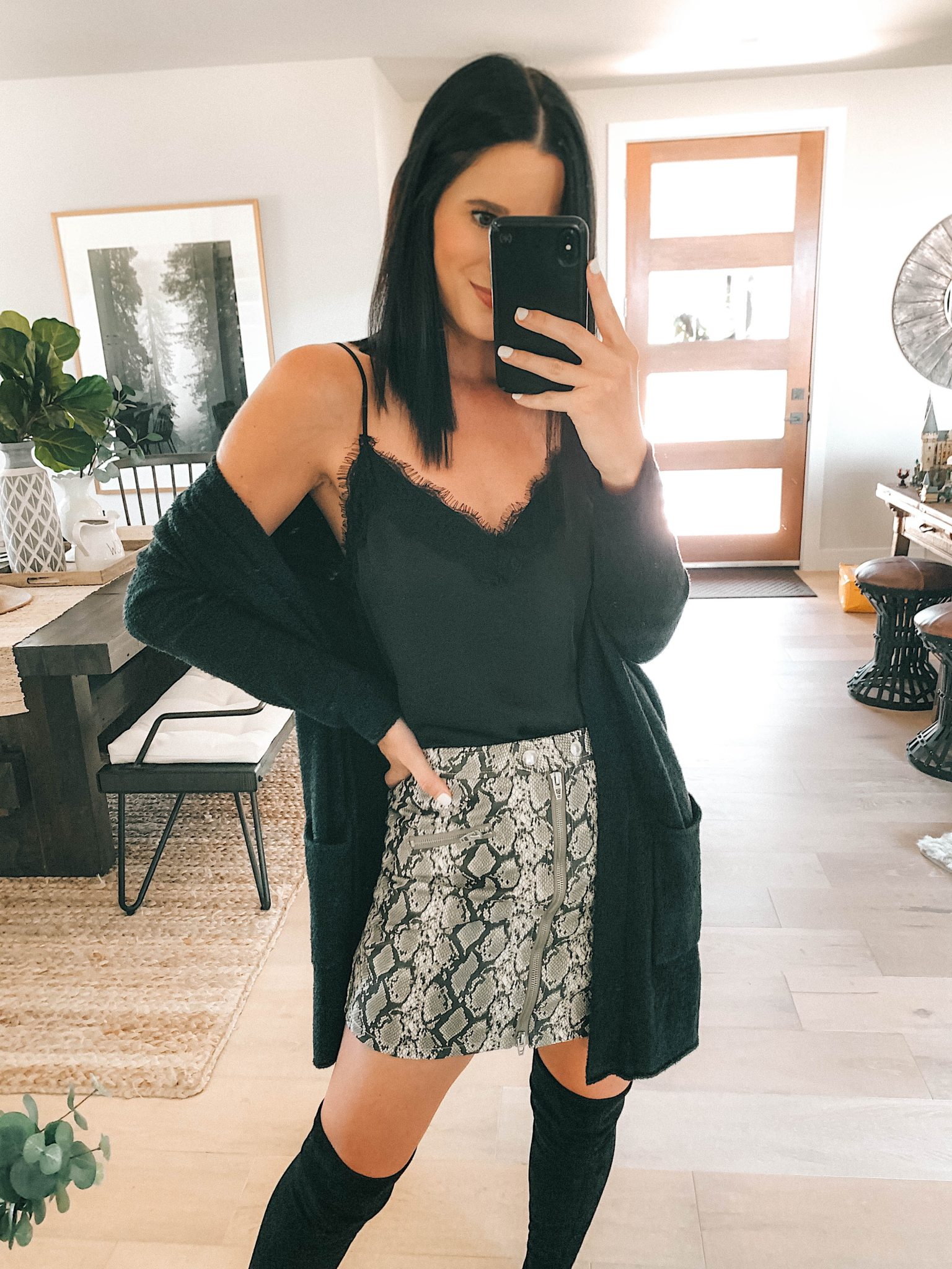 Create a Capsule Wardrobe with Nordstrom Anniversary Sale Pieces by popular Austin fashion blog, Dressed to Kill: image of a woman standing in her house and wearing a Nordstrom BlankNYC Snakeskin Mini Skirt, Barefoot Dreams Cardigan, Steve Madden Over the Knee Boots and BP Lace Cami.