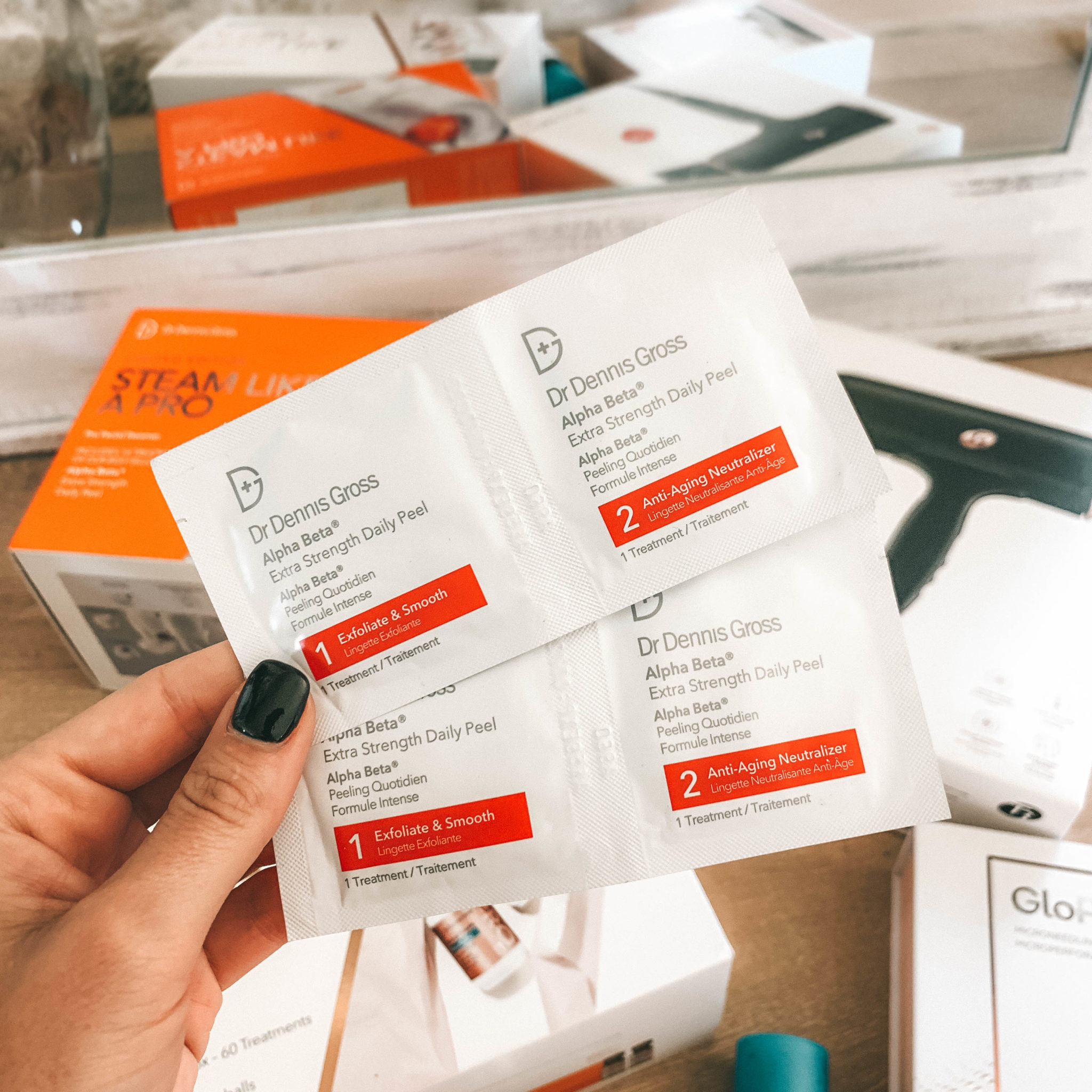Must Have Beauty Buys from the Nordstrom Anniversary Sale by popular Austin beauty blog, Dressed to Kill: image of a woman holding Dr. Dennis Gross Extra Strength Daily Peel packets.