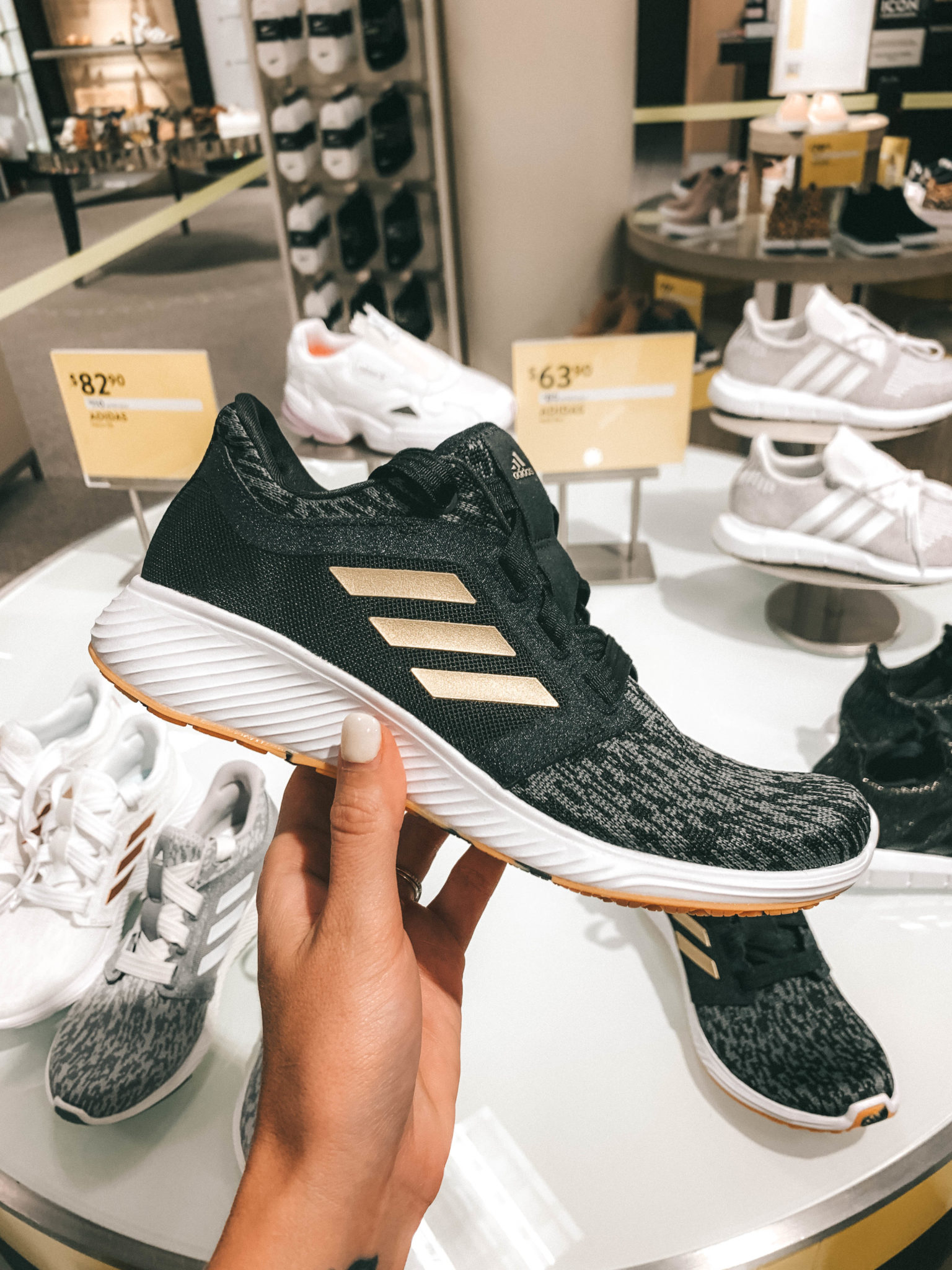 Top 11 Must Have Pieces from the Nordstrom Anniversary Sale by popular Austin fashion blog, Dressed to Kill: image of a woman holding a pair of black Edge Lux 3 Running Shoe by ADIDAS
