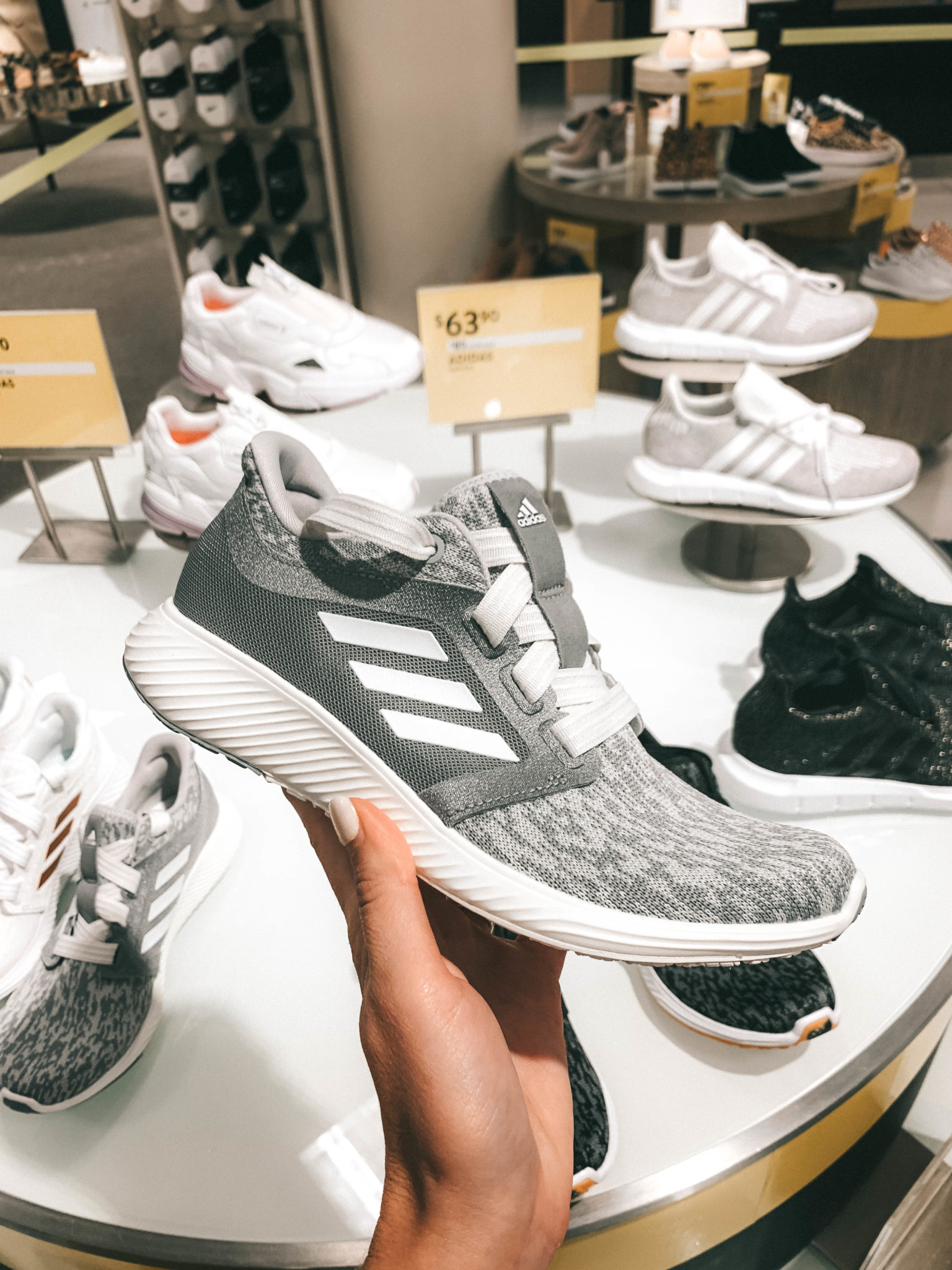 Top 11 Must Have Pieces from the Nordstrom Anniversary Sale by popular Austin fashion blog, Dressed to Kill: image of a woman holding a grey Edge Lux 3 Running Shoe by ADIDAS