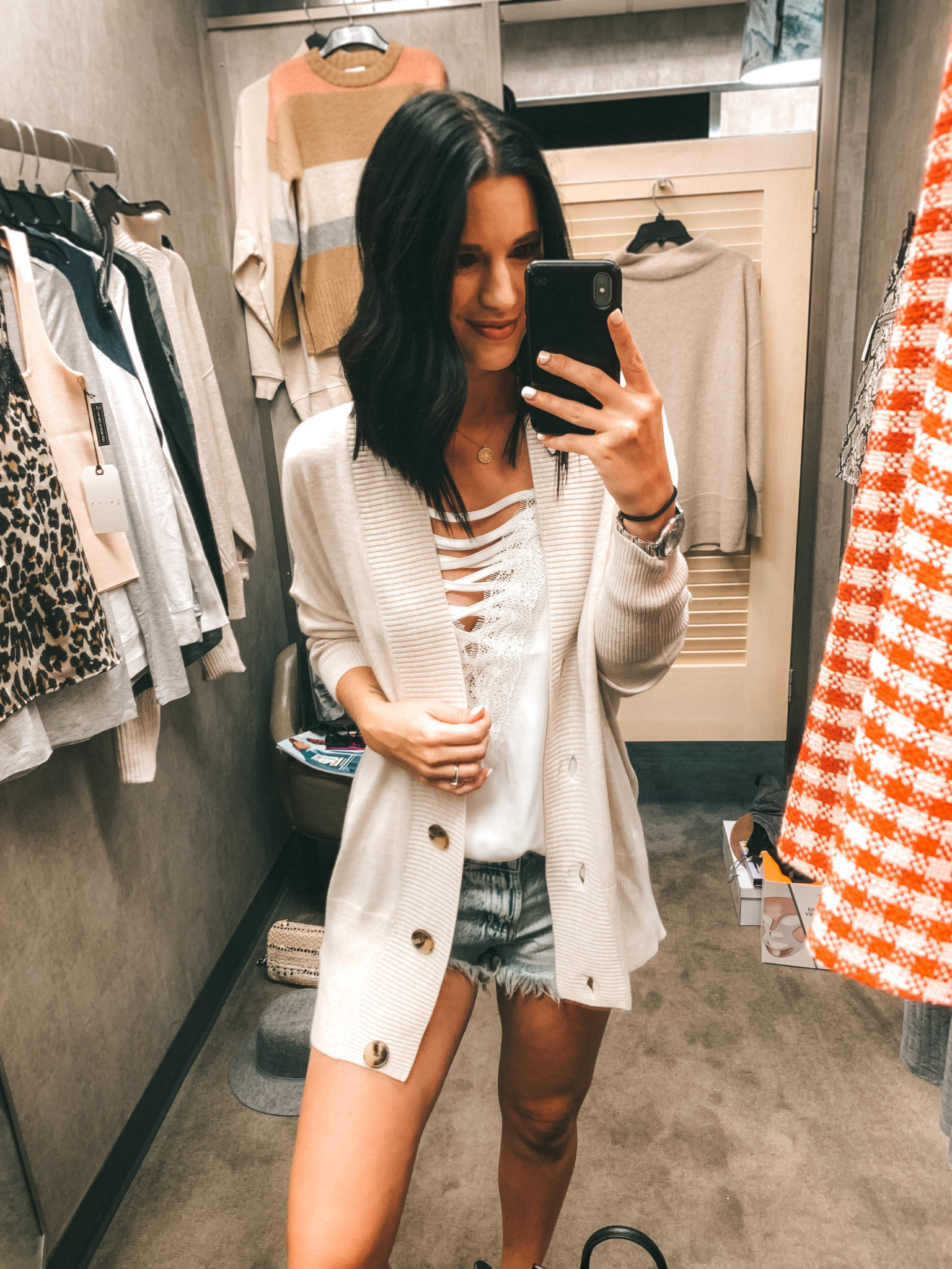 Top 11 Must Have Pieces from the Nordstrom Anniversary Sale by popular Austin fashion blog, Dressed to Kill: image of a woman standing in a Nordstrom dressing room and wearing a Barefoot Dreams Cardigan.