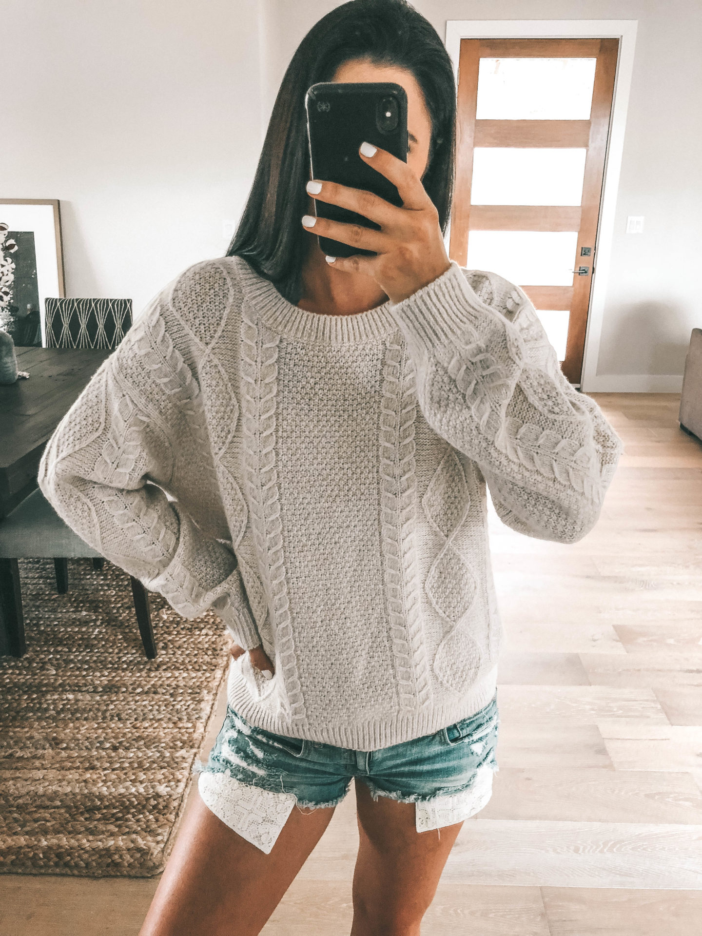 Tips on How to Shop the 2019 Nordstrom Anniversary SALE by popular fashion blog, Dressed to Kill: image of a woman taking a selfie with her smartphone and wearing a woven cable knit sweater and cut off denim shorts.