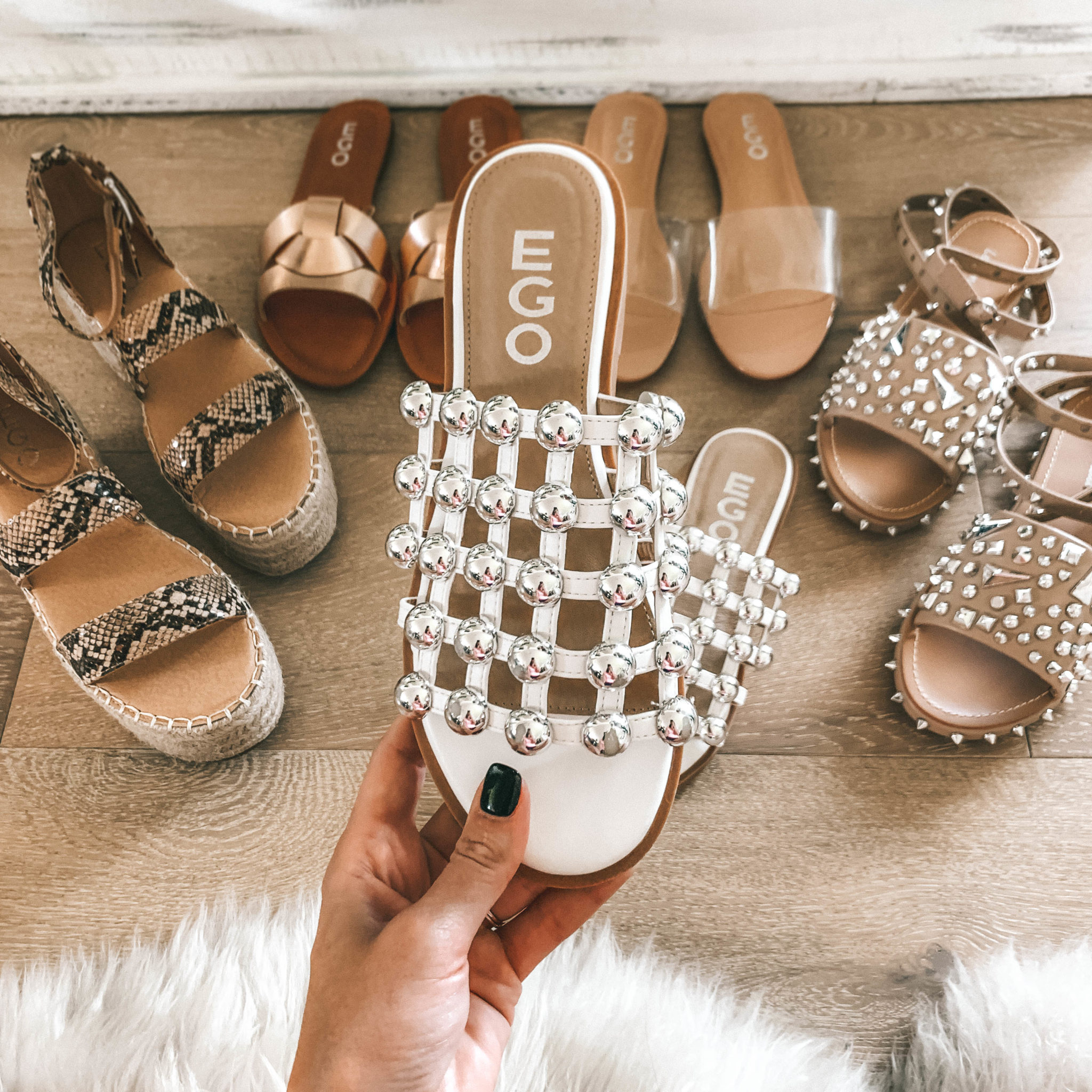 5 Must Have Affordable EGO Sandals for Summer by popular Austin fashion blog, Dressed to Kill: image of woman holding EGO sandals Hazel Silver Studded Detail Slider In White Faux Leather
