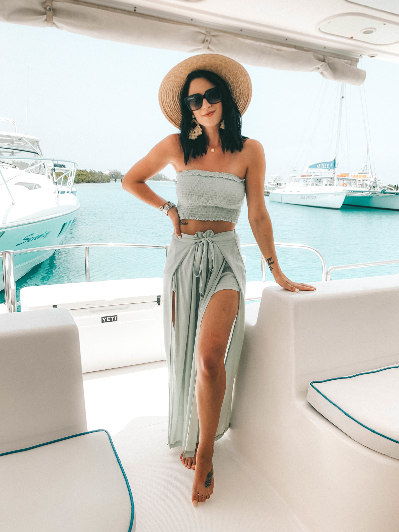 Amaryllis Apparel Abroad Turks & Caicos Summer Try-On by popular Austin fashion blog, Dressed to Kill: image of a woman standing on a boat in Turks and Caicos and wearing an Amaryllis Apparel Aruba set.