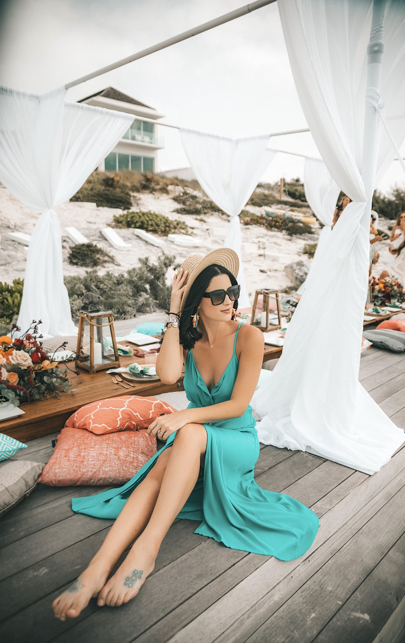 Amaryllis Apparel Abroad Turks & Caicos Summer Try-On by popular Austin fashion blog, Dressed to Kill: image of a woman sitting outside on the beach in Turks and Caicos and wearing a turquoise Amaryllis Apparel Telia button maxi dress.