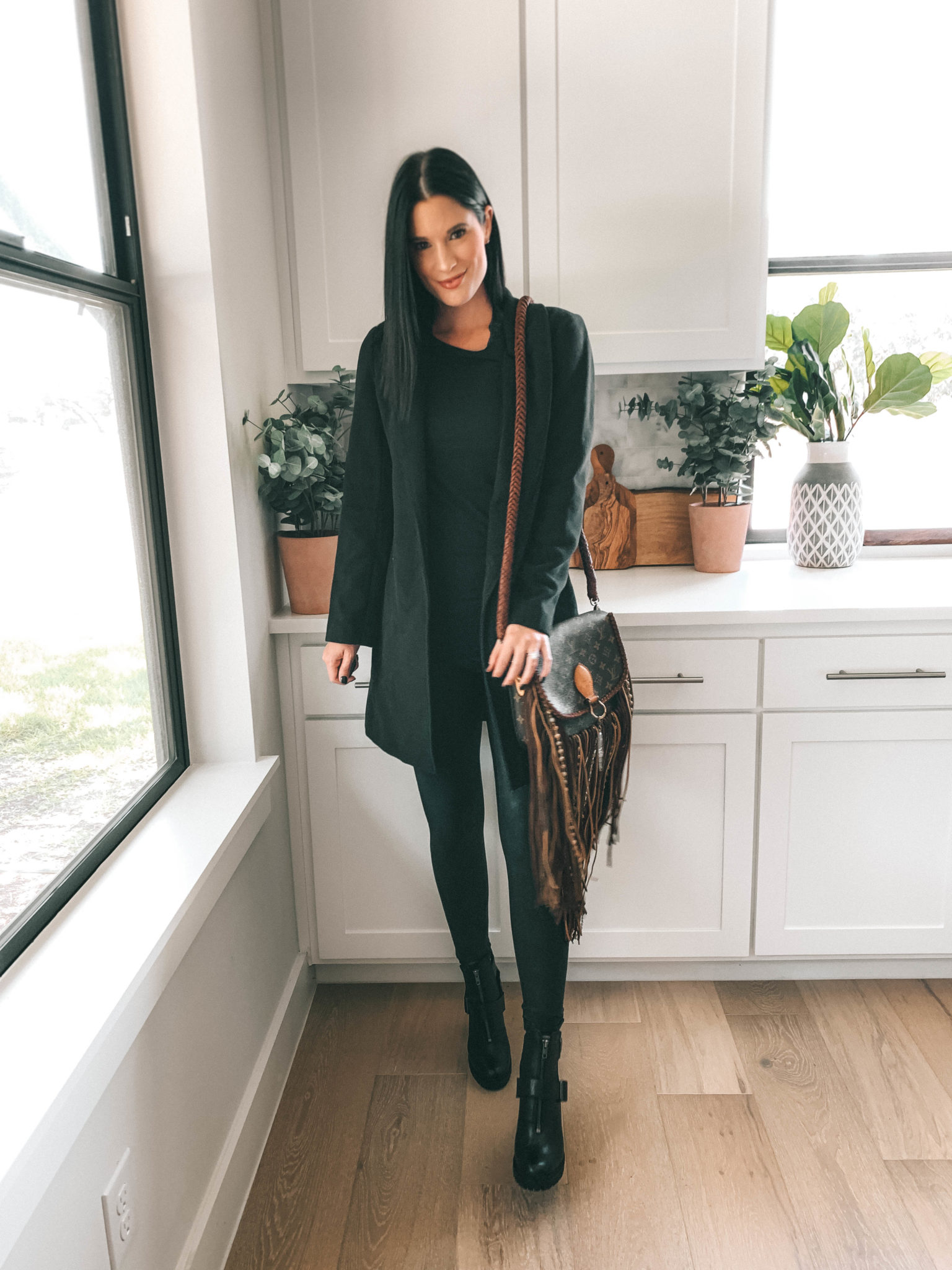 How to Style an All Black Outfit 3 Different Ways by popular Austin blog, Dressed to Kill: image of woman standing in her kitchen and wearing a black Halogen Double Face Coat, black Spanx Faux Leather Leggings, and carrying a World Traveler Dirty Blonde purse.
