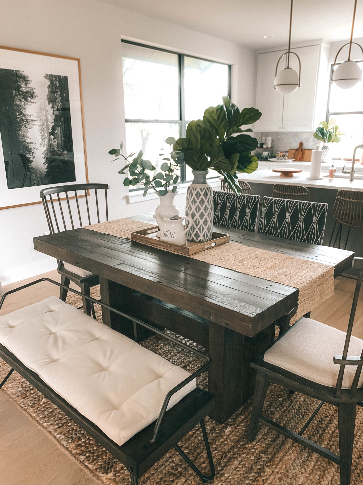 "Stunning Summer Dining Room Decorating Ideas by popular Austin lifestyle blog, Dressed to Kill: image of a dining room decorated with a West Elm Chestnut Emmerson® Reclaimed Wood Dining Table, Wayfair Abigale Low Back Metal Bench, World Market Flynn counter stools, World Market Flynn area rug, Target Threshold Tan Natural Ramie Table Runner (72""X14""), West Elm Reclaimed Wood Trays, MacKenzie-Childs Sweetbriar Vase, RAE DUNN ARTISAN NOURISH WATER PITCHER, Minted Redwood Morning print, and Anthropologie White-Dipped Ladder."
