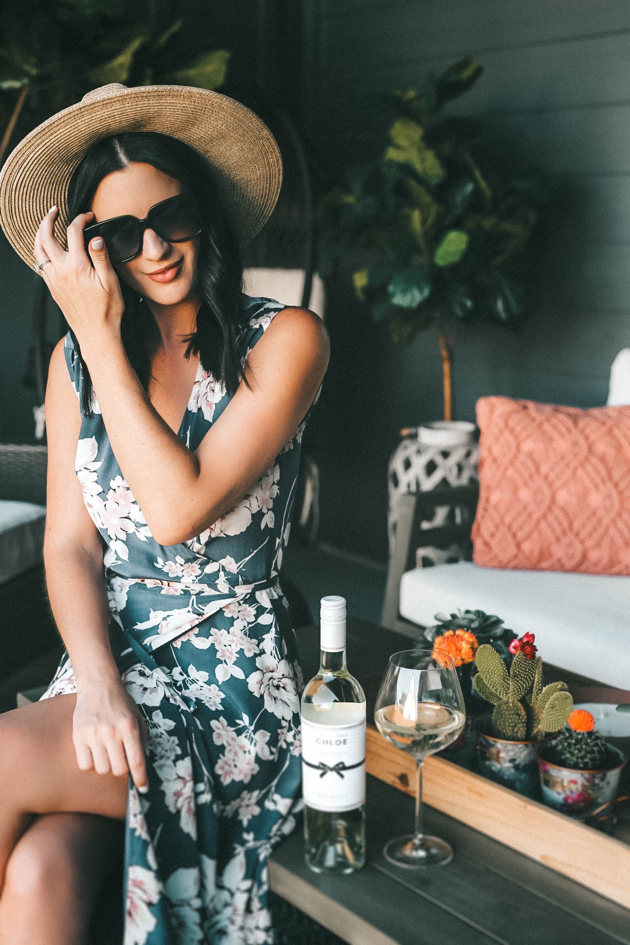 Celebrating Women in Film with Chloe Wine Collection by popular Austin life and style blog, Dressed to Kill: image of a woman sitting on her outdoor coffee table next to a bottle of Chloe pinot grigio wine and an empty wine glass.