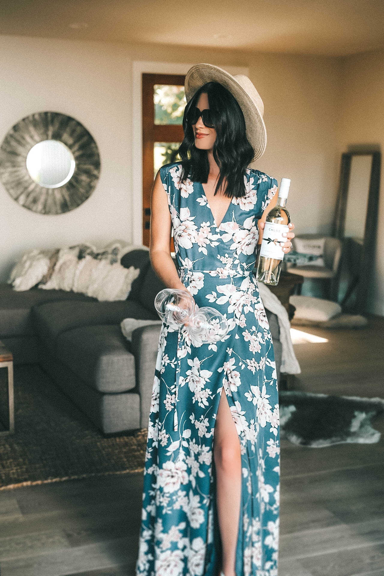 Celebrating Women in Film with Chloe Wine Collection by popular Austin life and style blog, Dressed to Kill: image of a woman in a blue floral dress and straw fedora hat holding a bottle of Chloe pinot grigio and a wine glass.