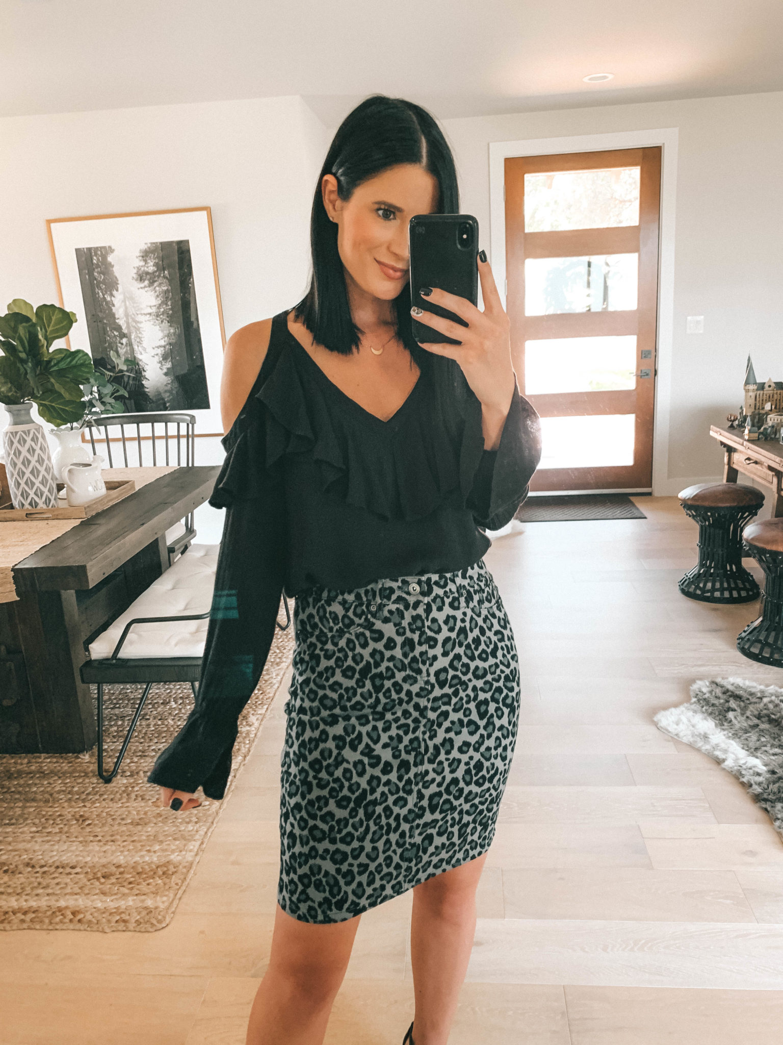 7 Affordable Fall Outfits from Walmart by popular Austin fashion blog, Dressed to Kill: image of a woman standing inside her house and wearing a black Walmart Sofia Jeans Cold-Shoulder Ruffle Neck Woven Top and Sofia Jeans Margarita Leopard Print Pencil Skirt.