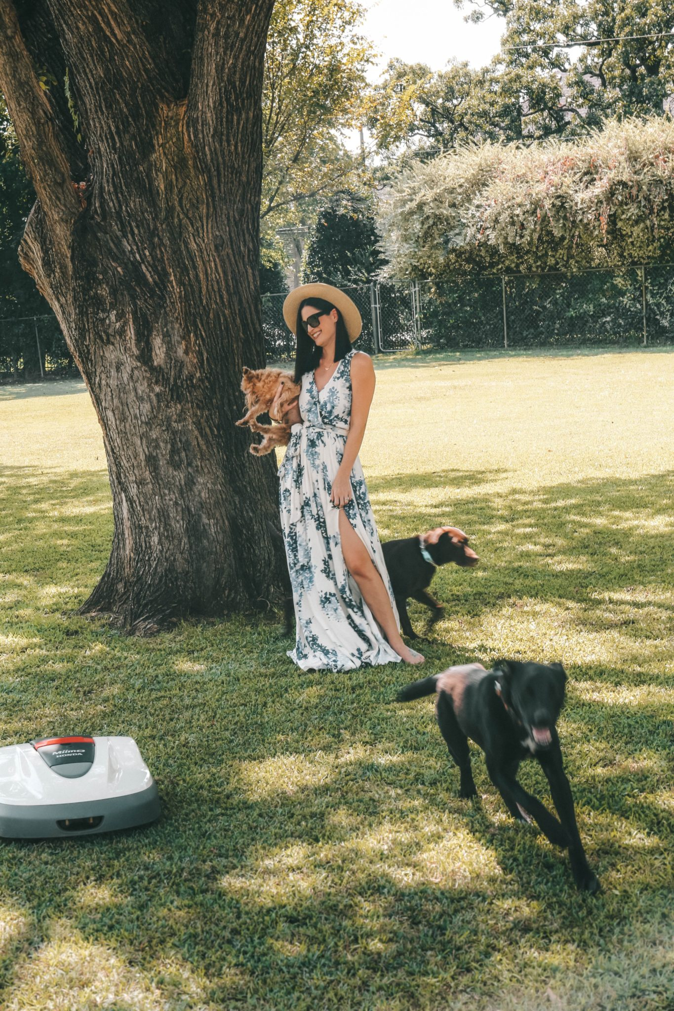 Honda Miimo Robotic Lawn Mower Review by popular Austin lifestyle blog, Dressed to Kill: image of woman and her dogs standing near the Honda Miimo Robotic Lawn Mower.