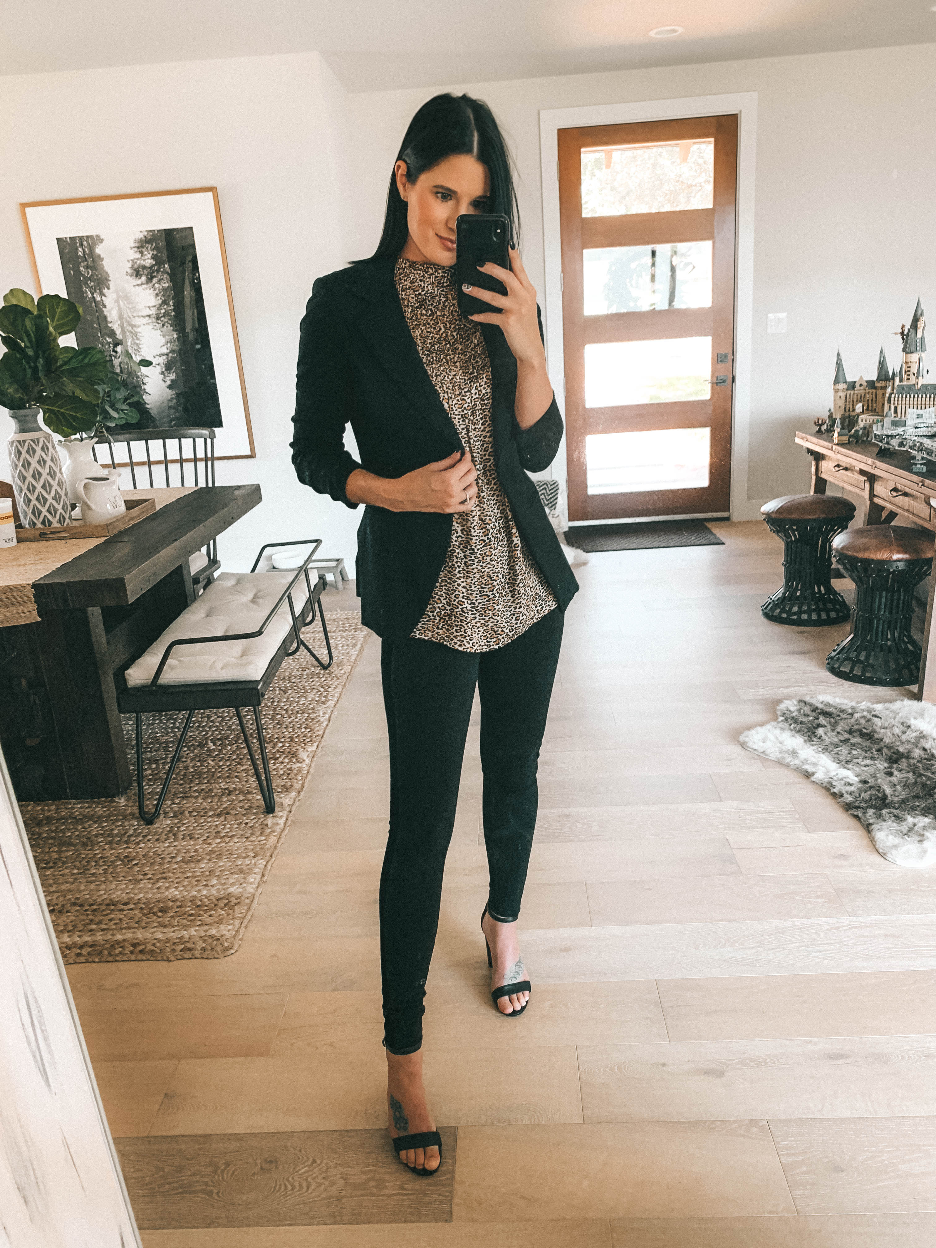 7 Affordable Fall Outfits from Walmart by popular Austin fashion blog, Dressed to Kill: image of a woman standing inside her house and wearing a leopard print Walmart Love Sadie Women's High Neck Sleeveless Blouse and Time and Tru Women's Velour Stripe Ponte Pants.